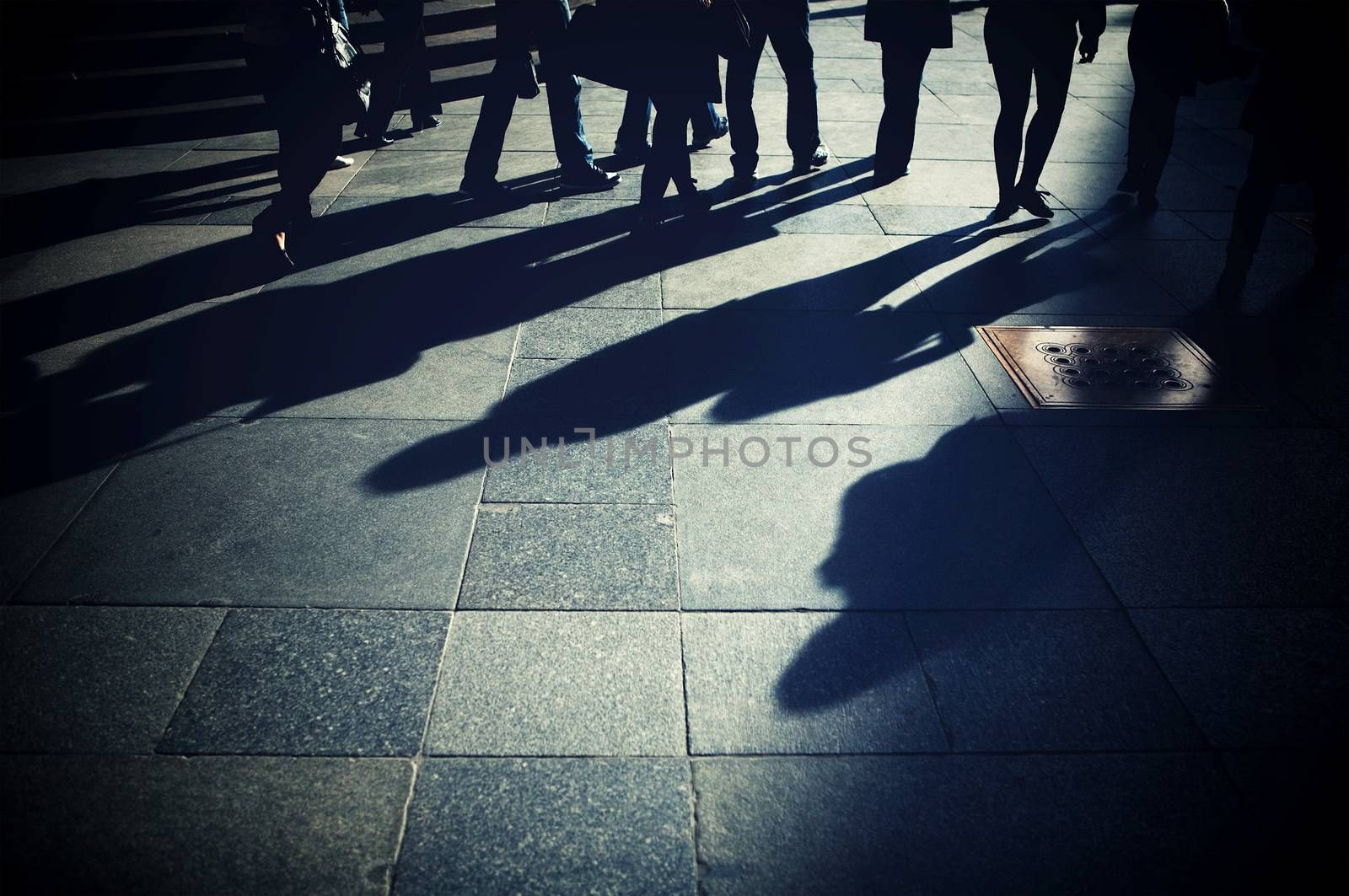 Shadows of people on the pavement. People walking the street.