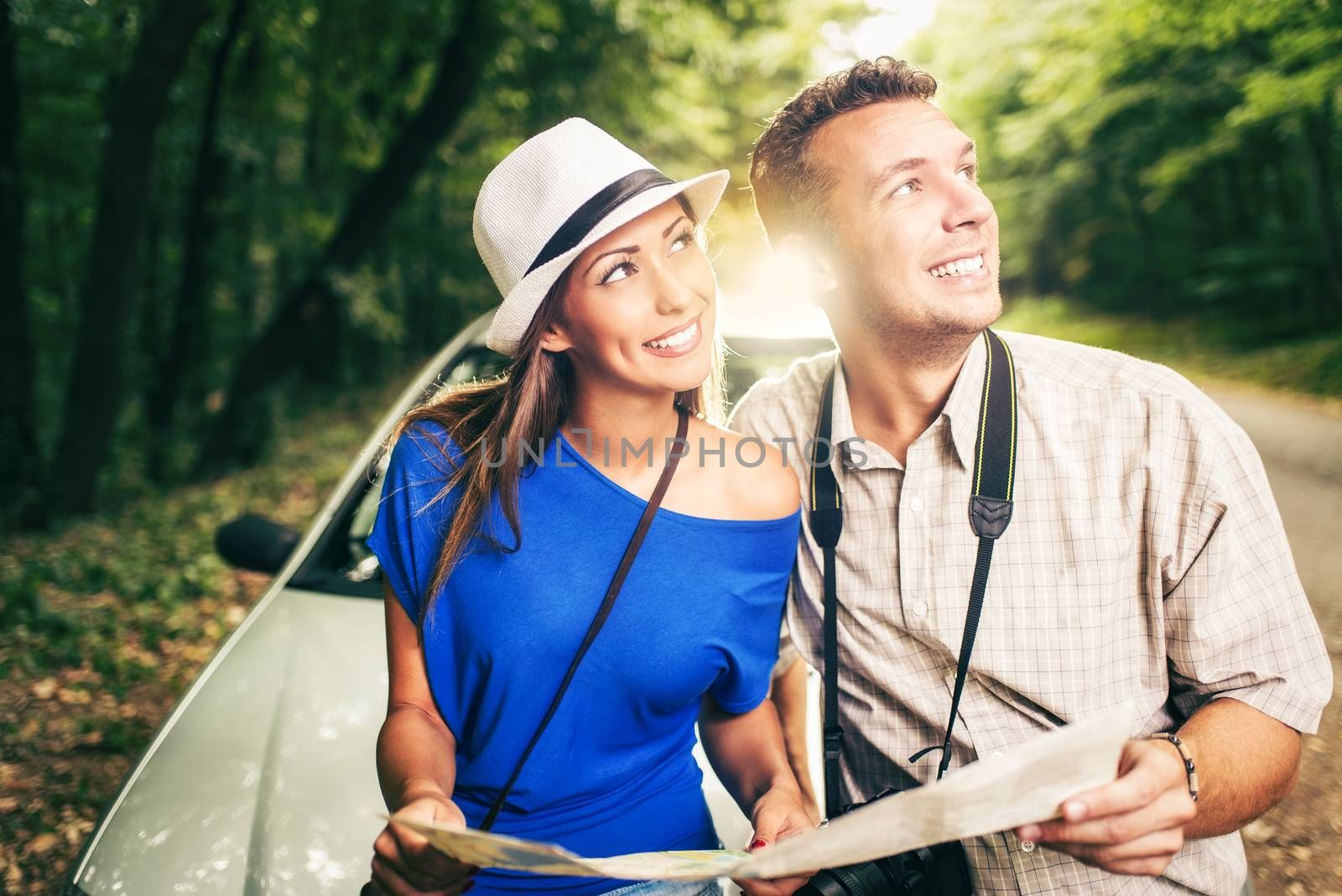 Young travelers standing before a car in the forest, holding map and looking at destination.