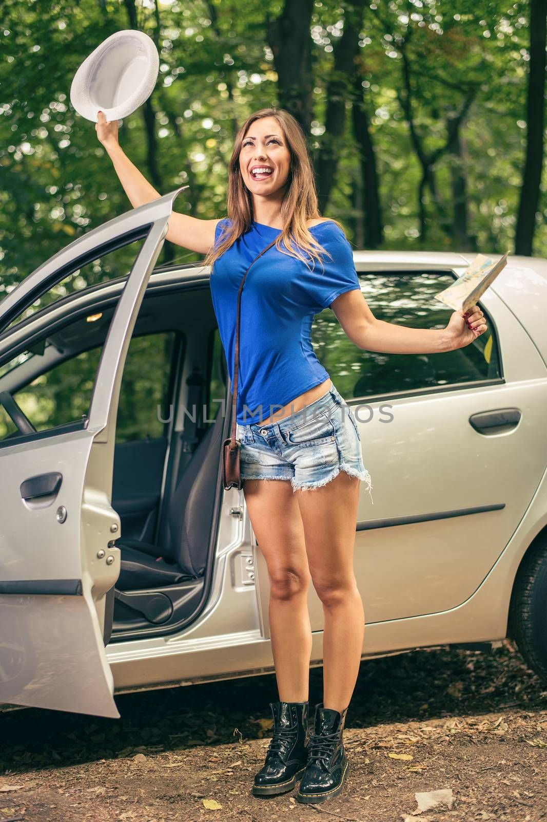 Cheerful woman on travel standing in front car  with arms raised and holding map.