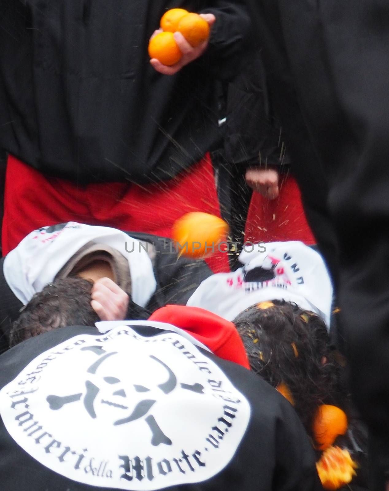ITALY, Ivrea: People are hit with fruit during the battle of oranges on February 7, 2016, in Ivrea, Italy.An estimated 7,000 people turned out to pelt each other at the historic festival. 70 people were injured by the flying fruit.