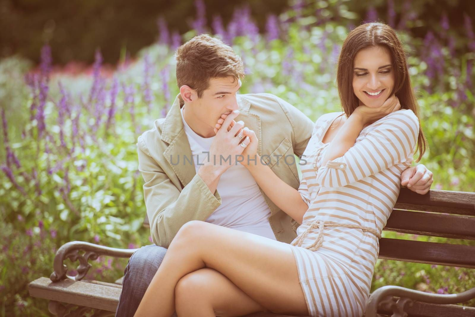 Loving young couple flirting while sitting at a park bench.