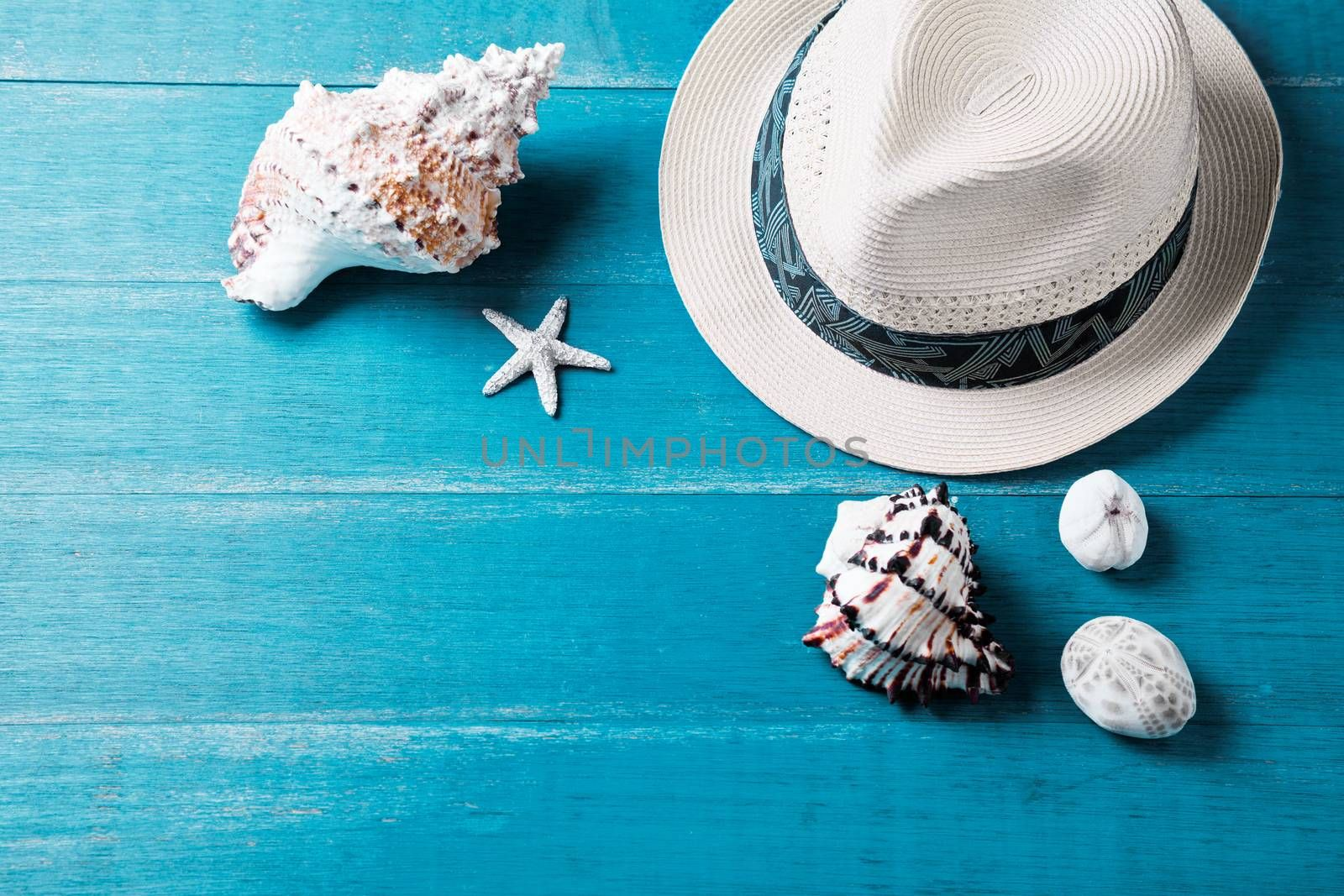 Summer hat and sea shells on a wooden table