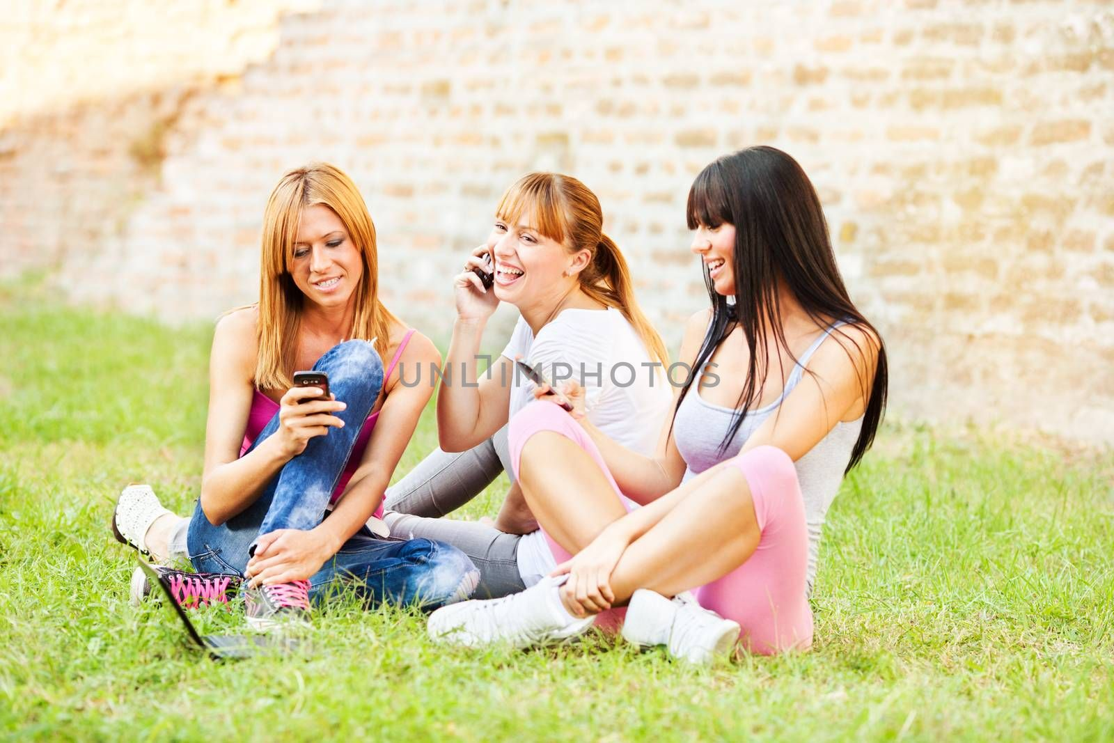 Three young beautiful girls communicate with cell phone outdoor