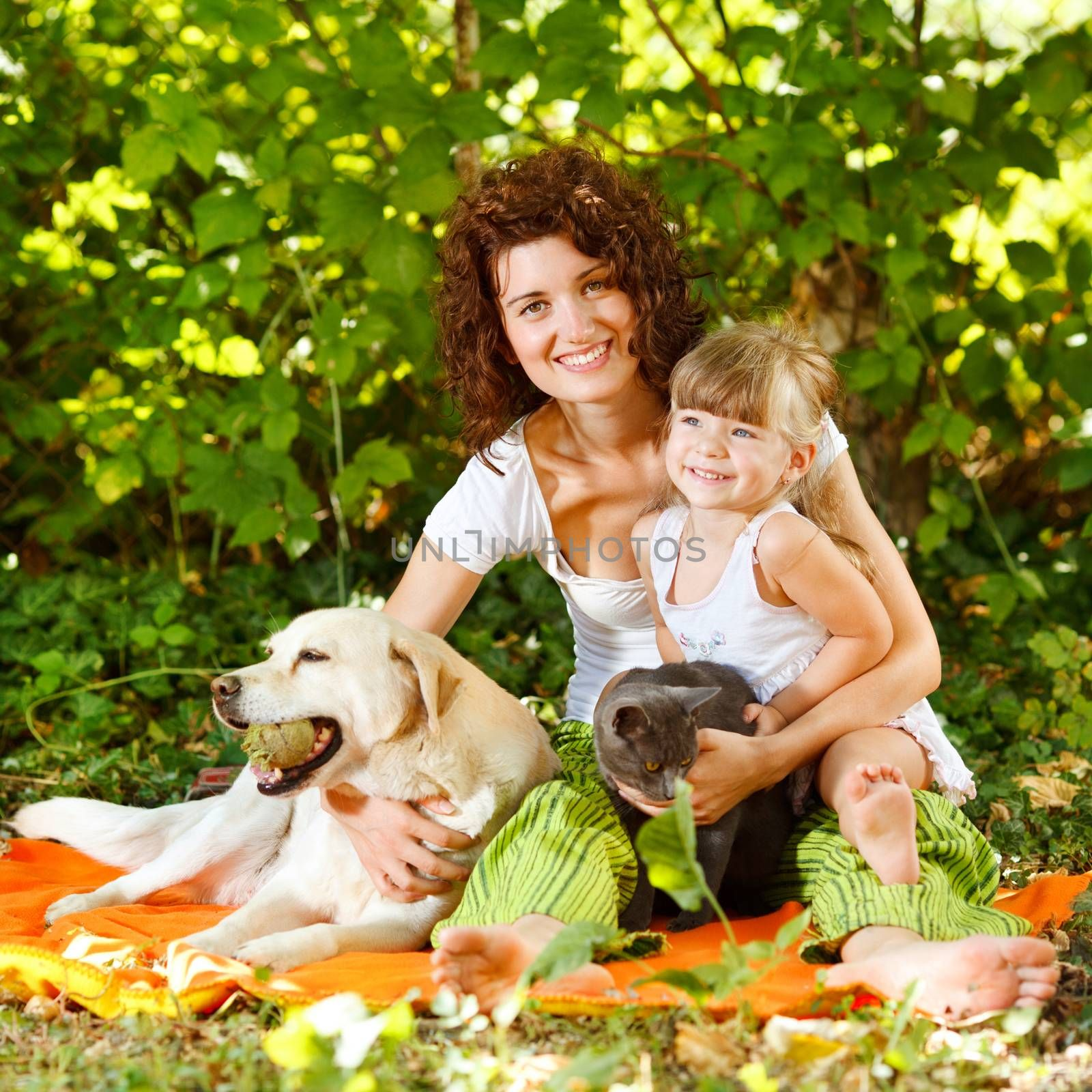 Beautiful mother and daughter relaxing in nature with pets
