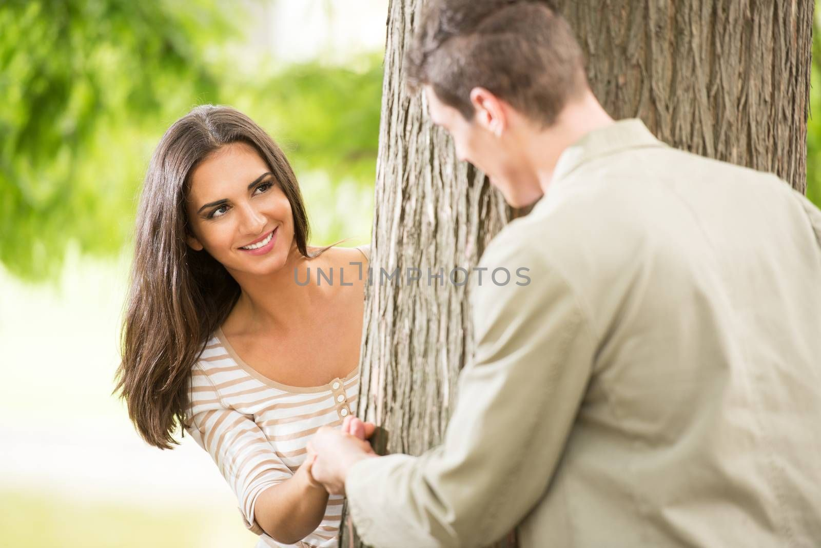 Beautiful girl in the park with her boyfriend enjoys playing hide behind a tree.