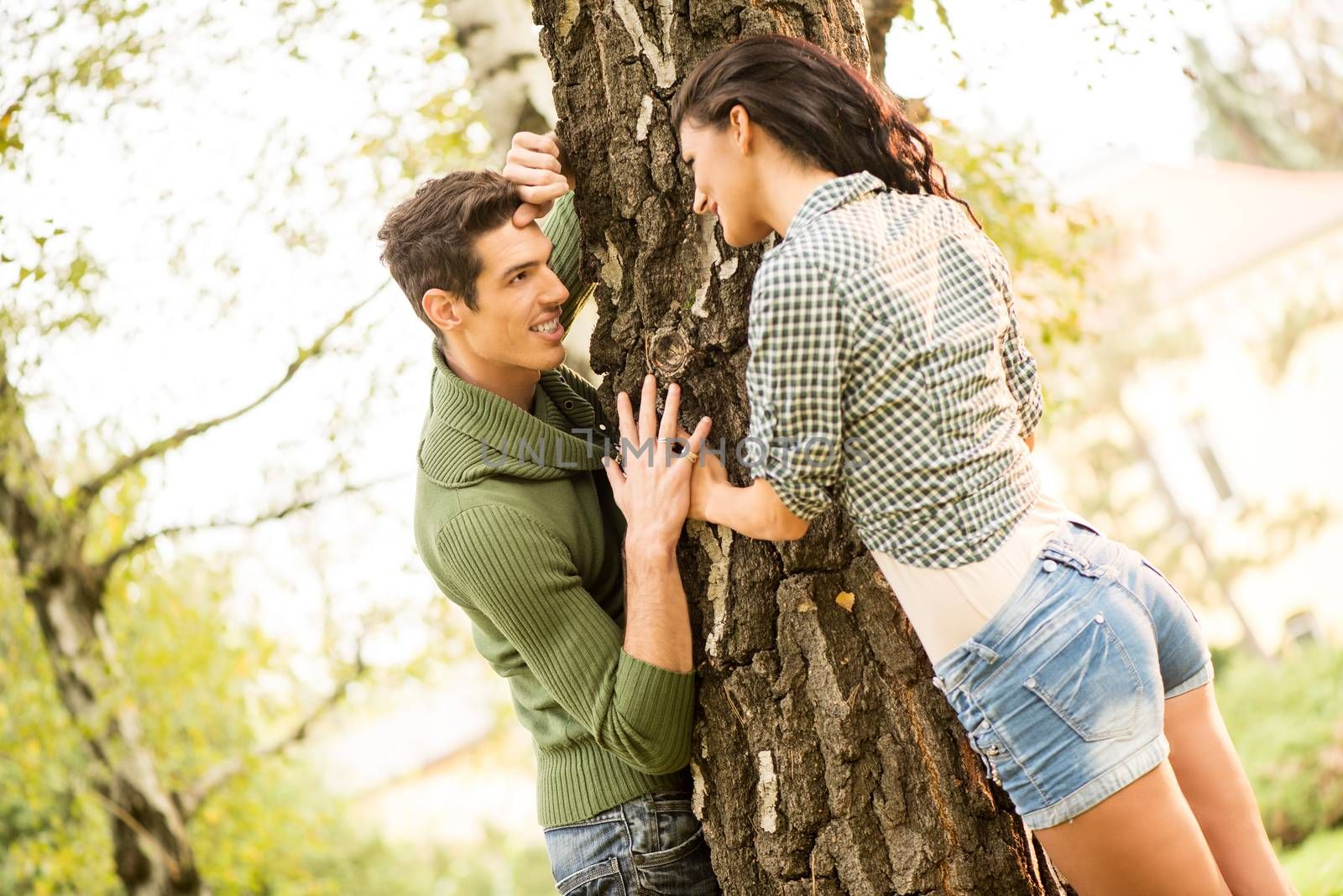 Young guy and girl in the park, play a romantic game of hiding by the tree.