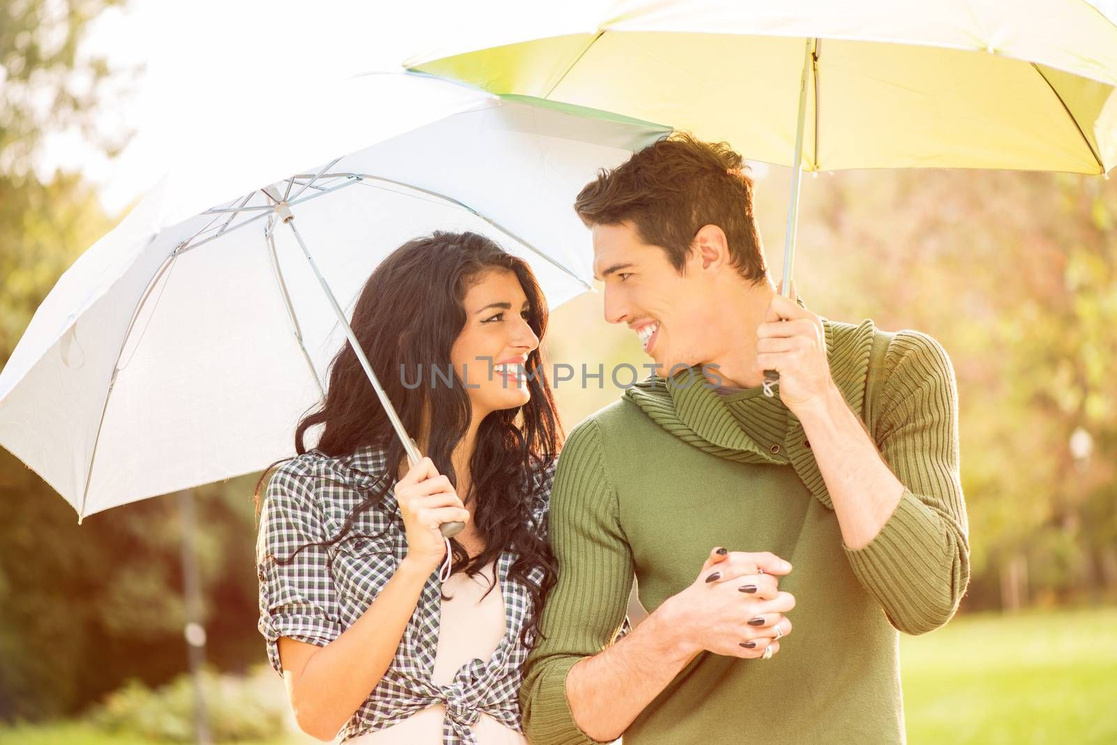 Young heterosexual couple walking in park holding hands and carrying umbrellas.
