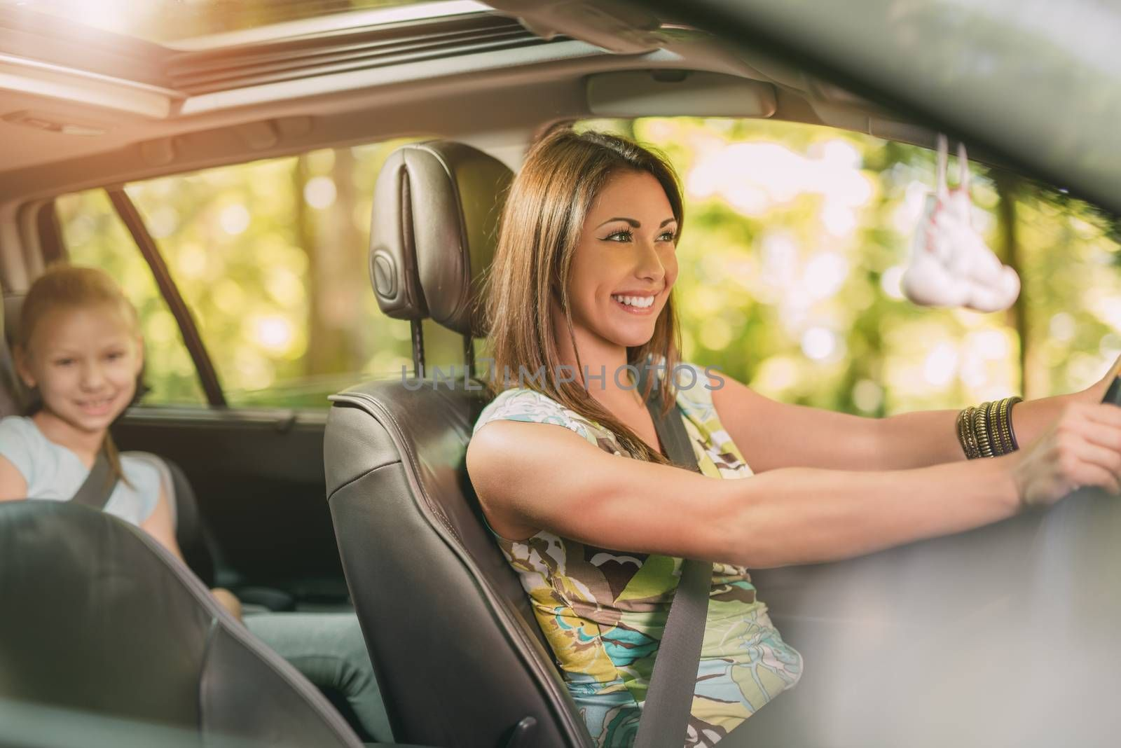 Young beautiful woman with a nice smile driving a car.  Her cute daughter sitting on rear and enjoying.