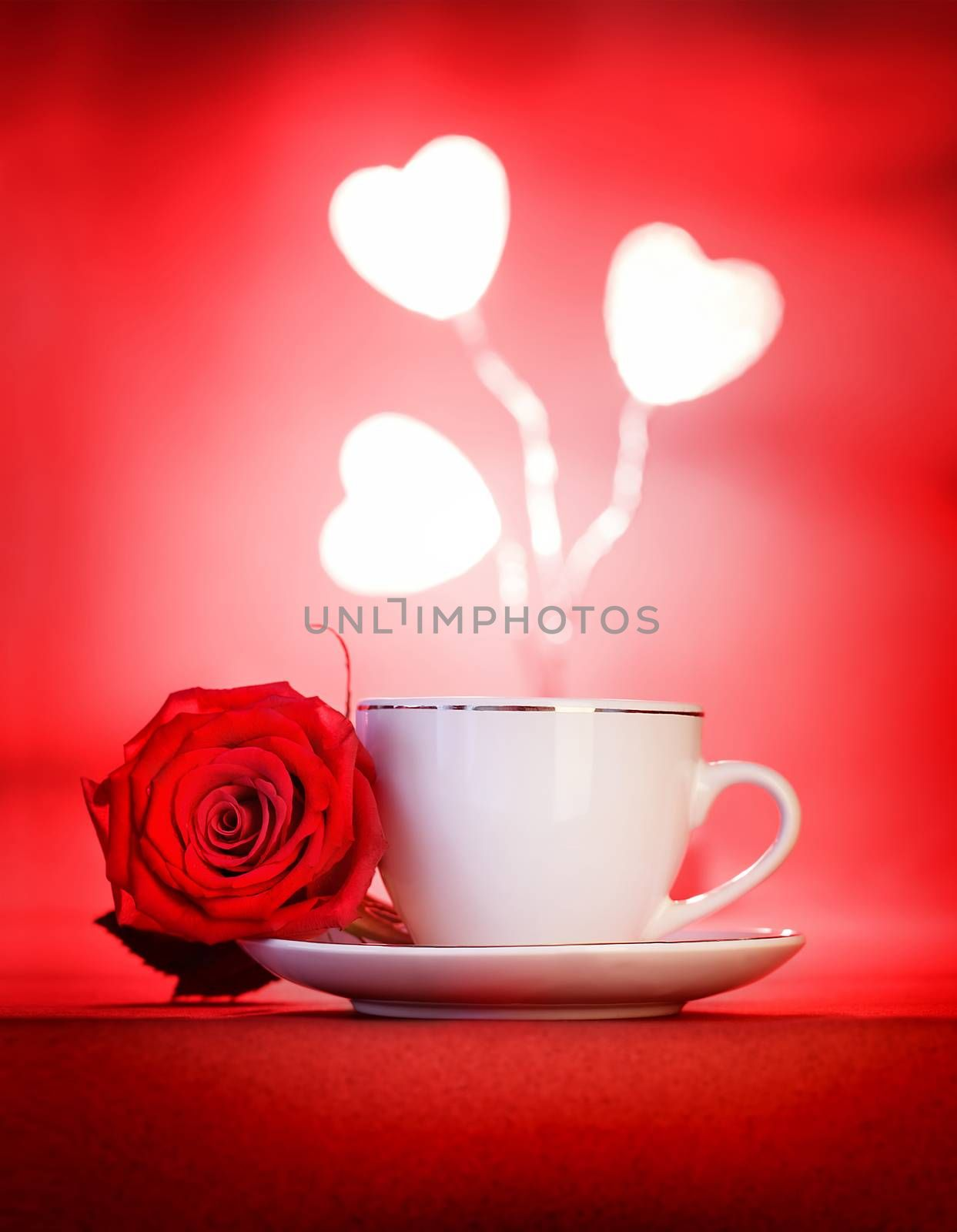 Cute little white cup of coffee with rose flower and hearts decoration over red background, romantic table setting, Valentine day celebration