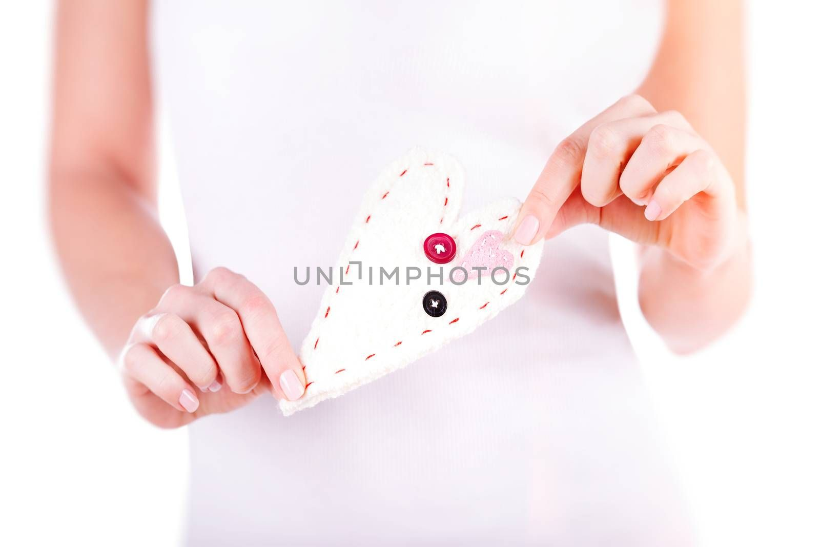 Woman holding in hands handmade sewn soft heart over white background, body part, great gift for Valentines day, love concept