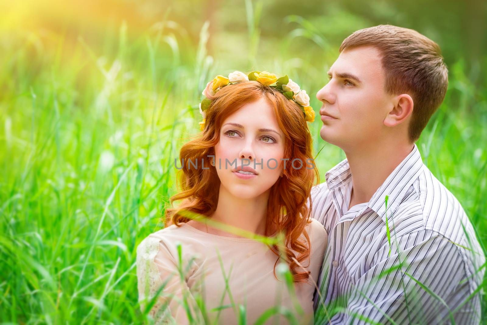 Portrait of a beautiful couple sitting in the park on a fresh green grass field and enjoying sunny day, romantic relationship