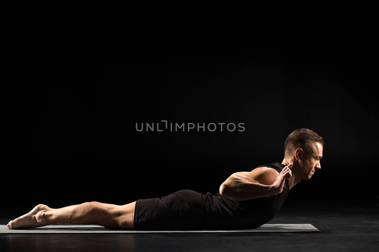 Young athletic man practicing yoga on yoga mat