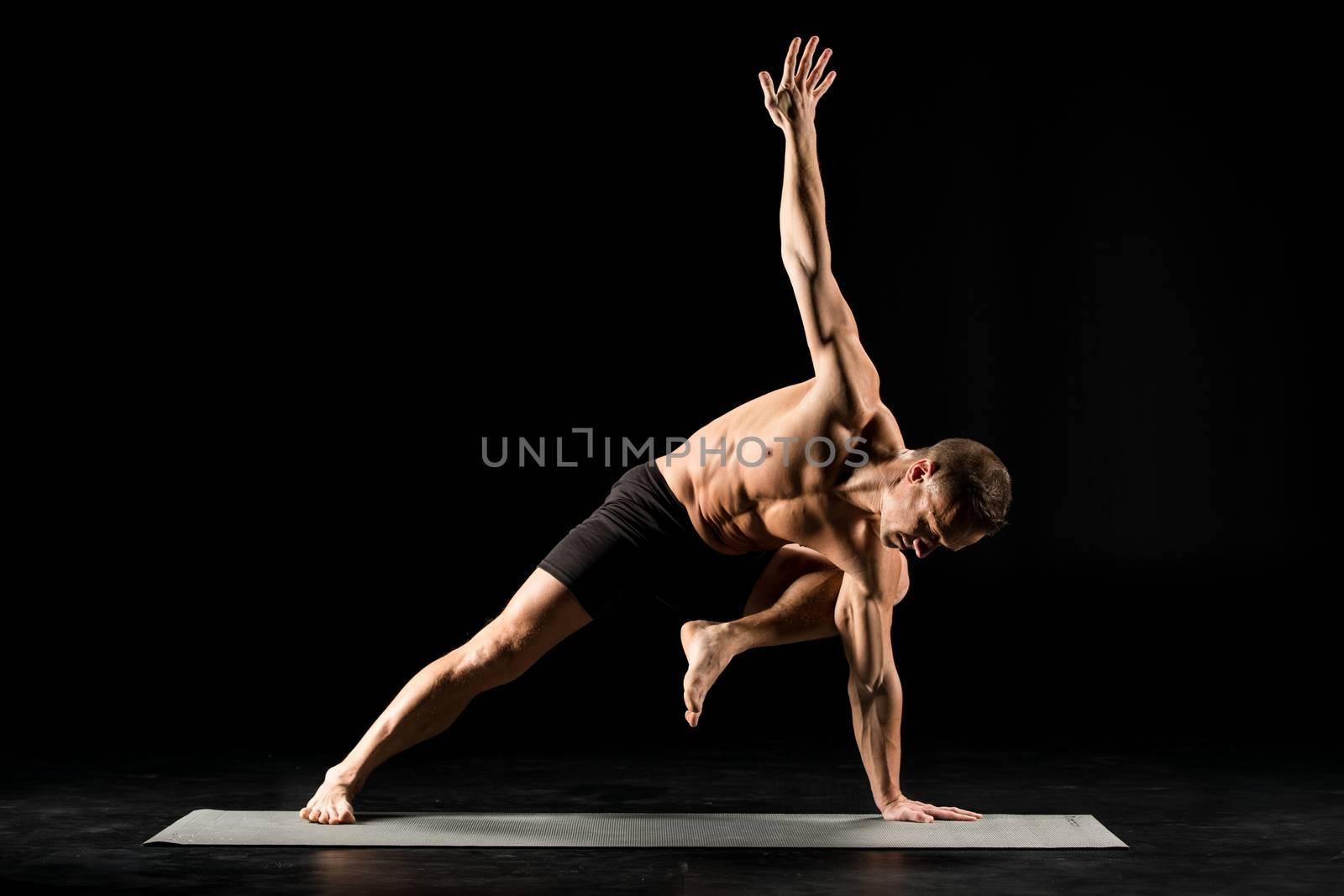 Young man practicing ashtanga vinyasa yoga exercise on yoga mat
