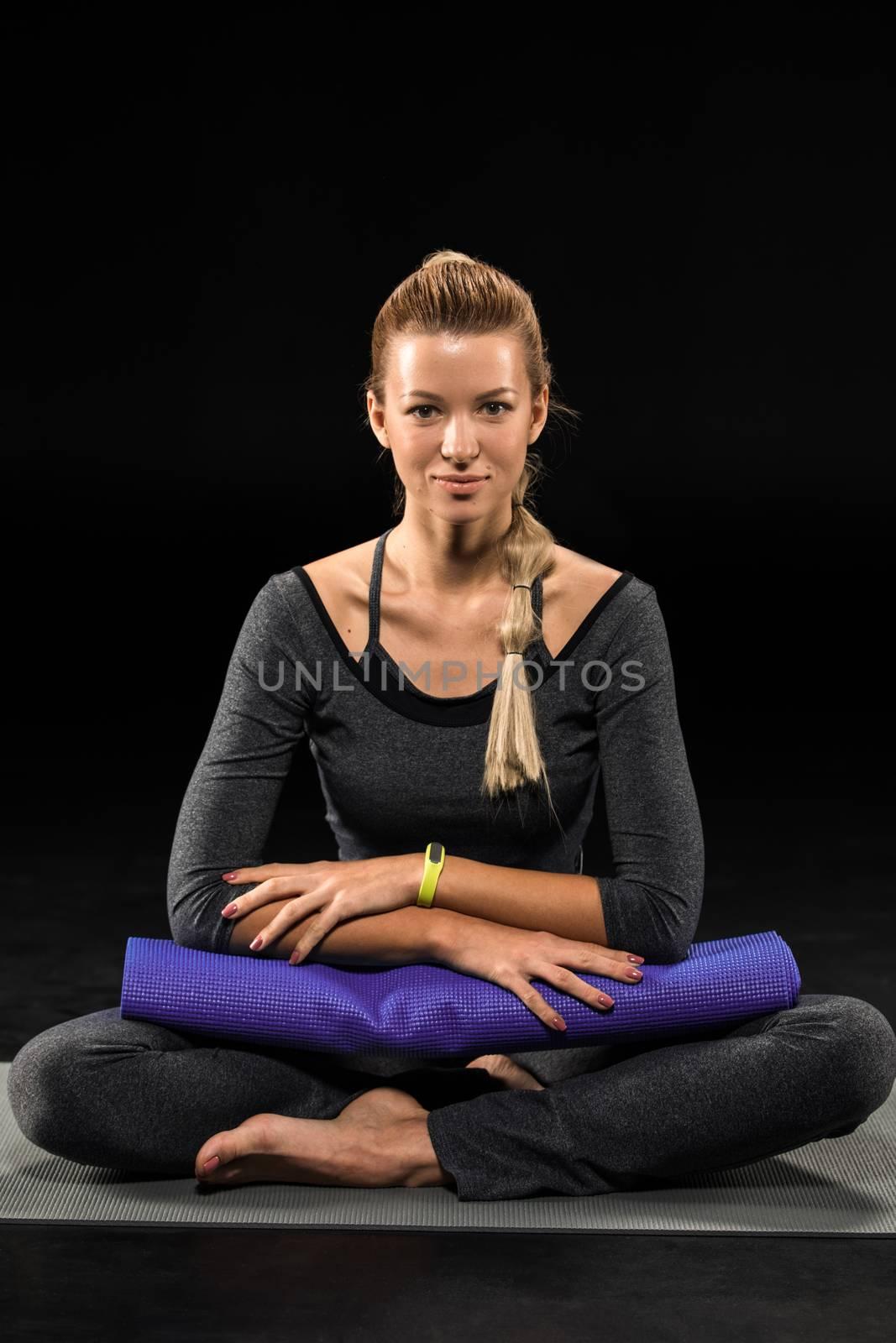 Sportswoman exercising yoga and holding yoga mat