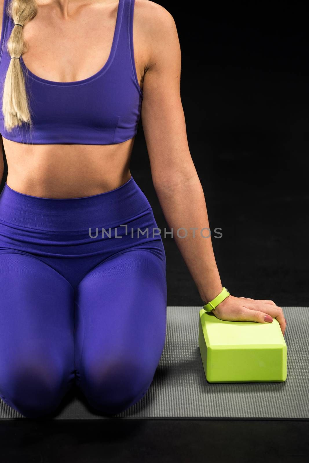 Partial view of sportswoman sitting on yoga mat and exercising with yoga block