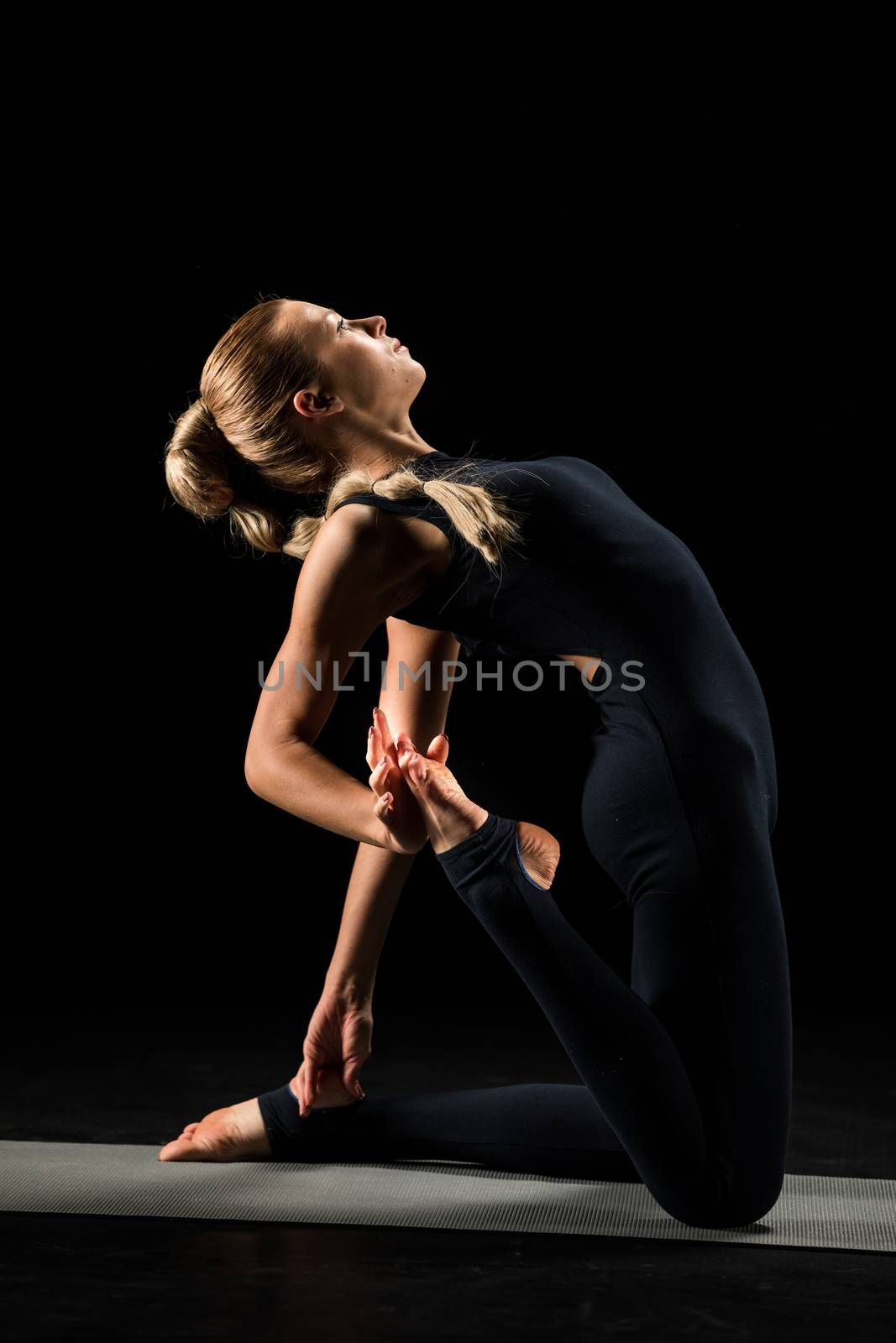 Woman practicing yoga and stretching on yoga mat