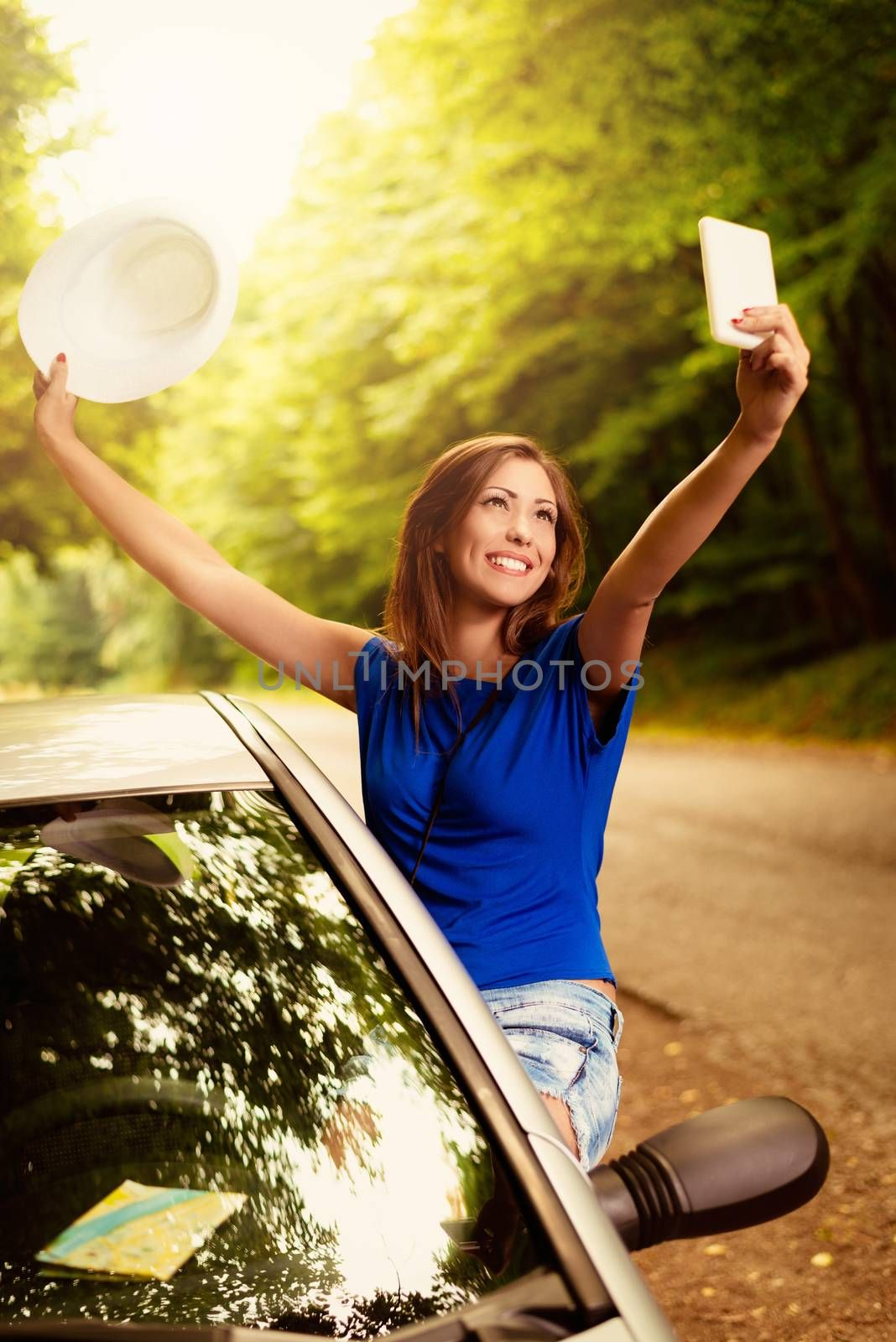 Cheerful woman on summer travel vacation leaning out of a car window. She is holding hat with arms raised and taking selfie.