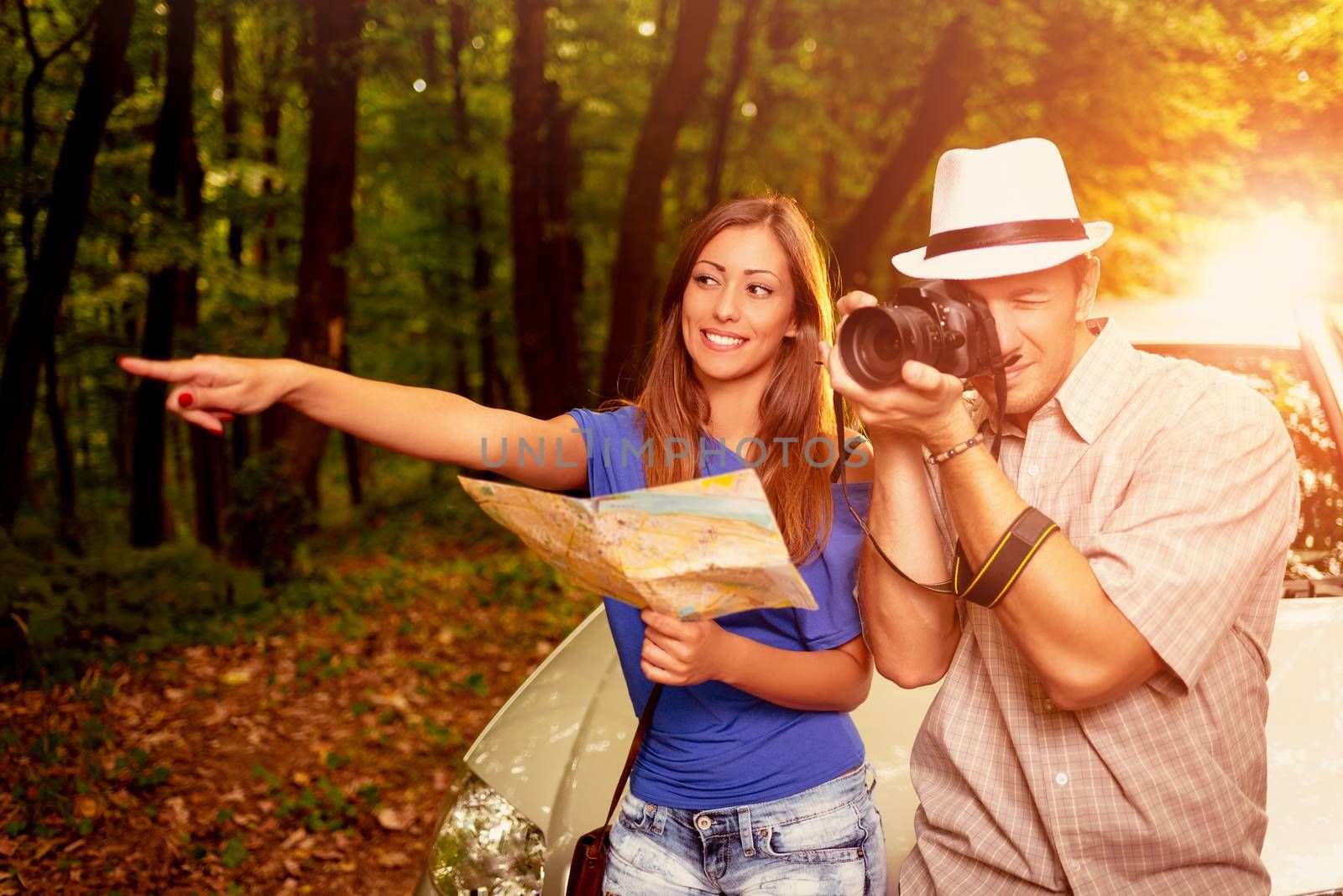 Young travelers standing before a car in the forest. Girl holding map and pointing destination. Guy taking a photo with digital camera.