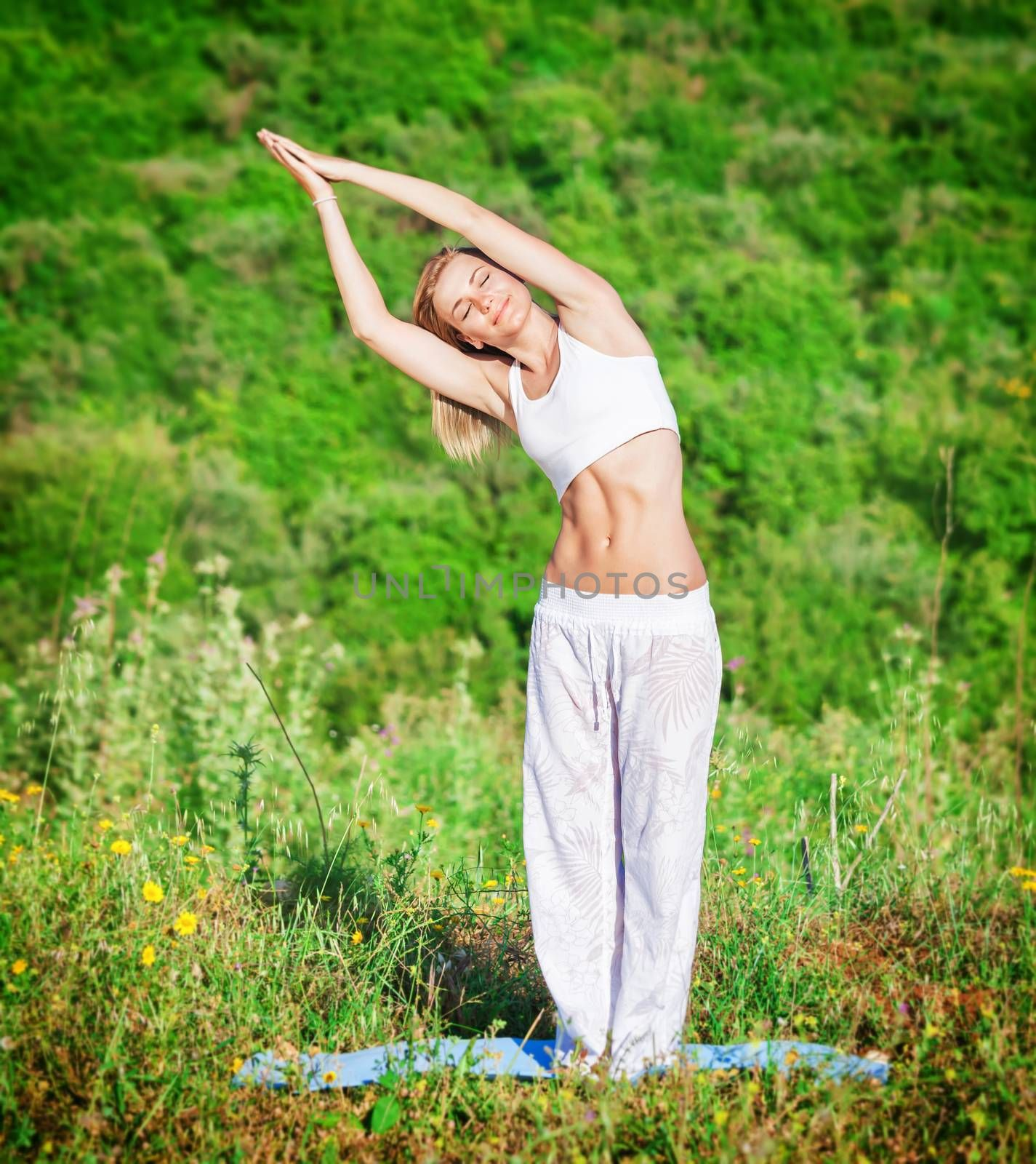 Woman doing exercise yoga outdoors in fresh green park on mountain background, with closed eyes slope in side, body and soul care