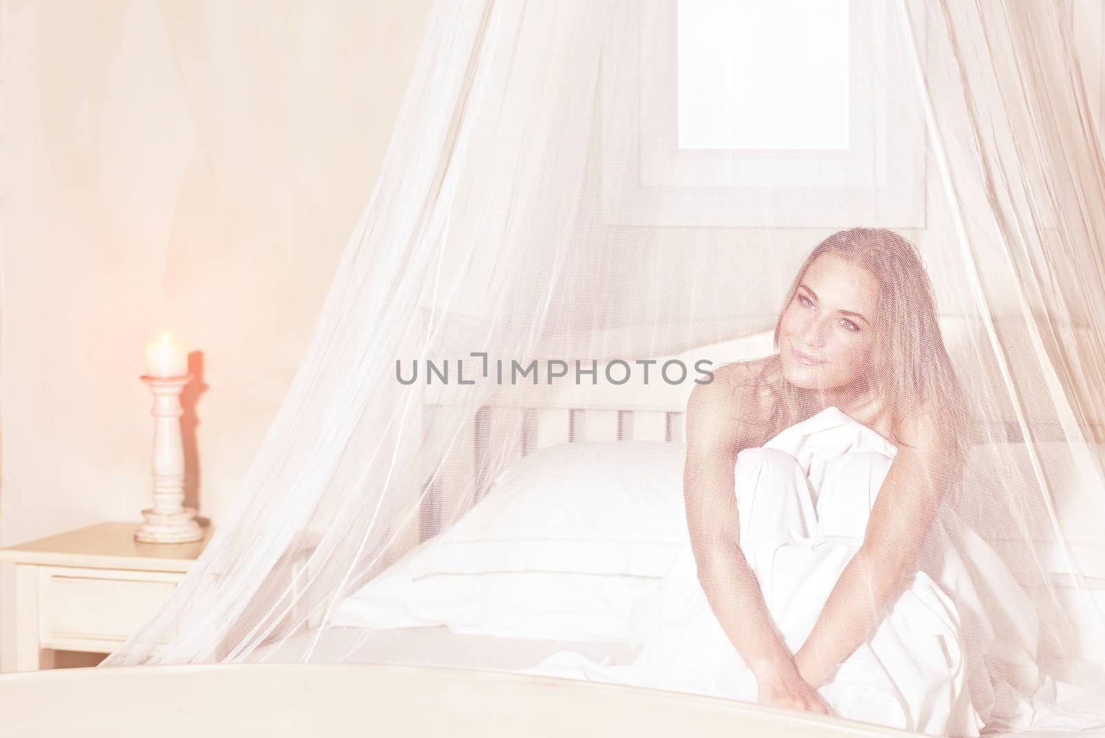 Romantic woman sitting in the bed under gentle transparent valance, spending weekend in luxury spa hotel, enjoying rest and relaxation