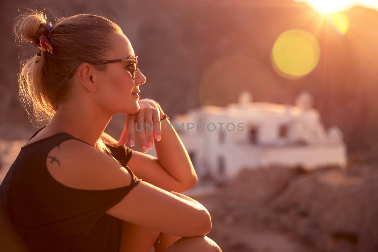 Beautiful woman enjoying spiritual travel to the wonderful place, sunset light scene, sitting on the mountains near the monastery, happy summer holidays