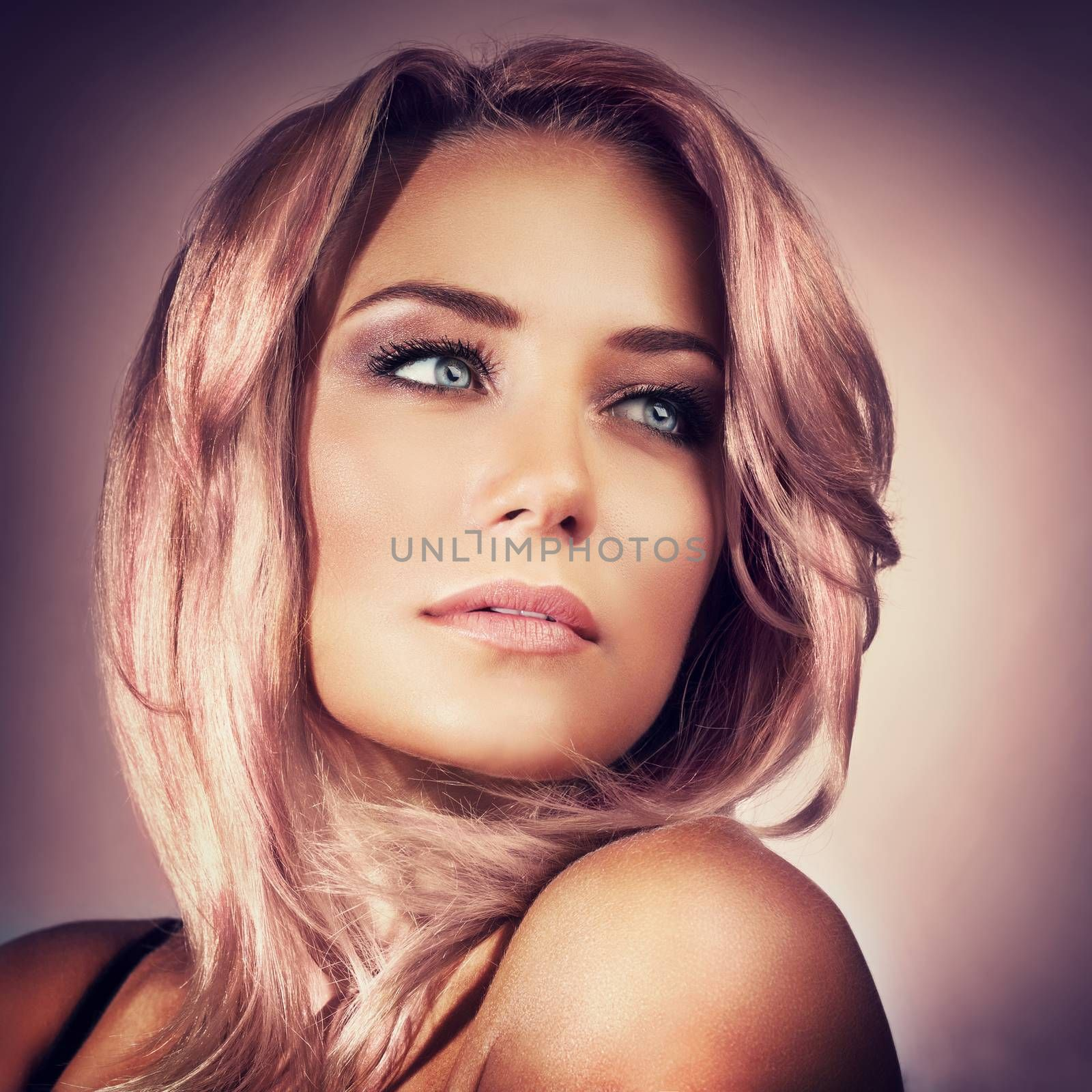 Closeup portrait of a beautiful sexy woman with trendy pink pastel hair color and smoky eyes makeup, face over purple background, fashionable look