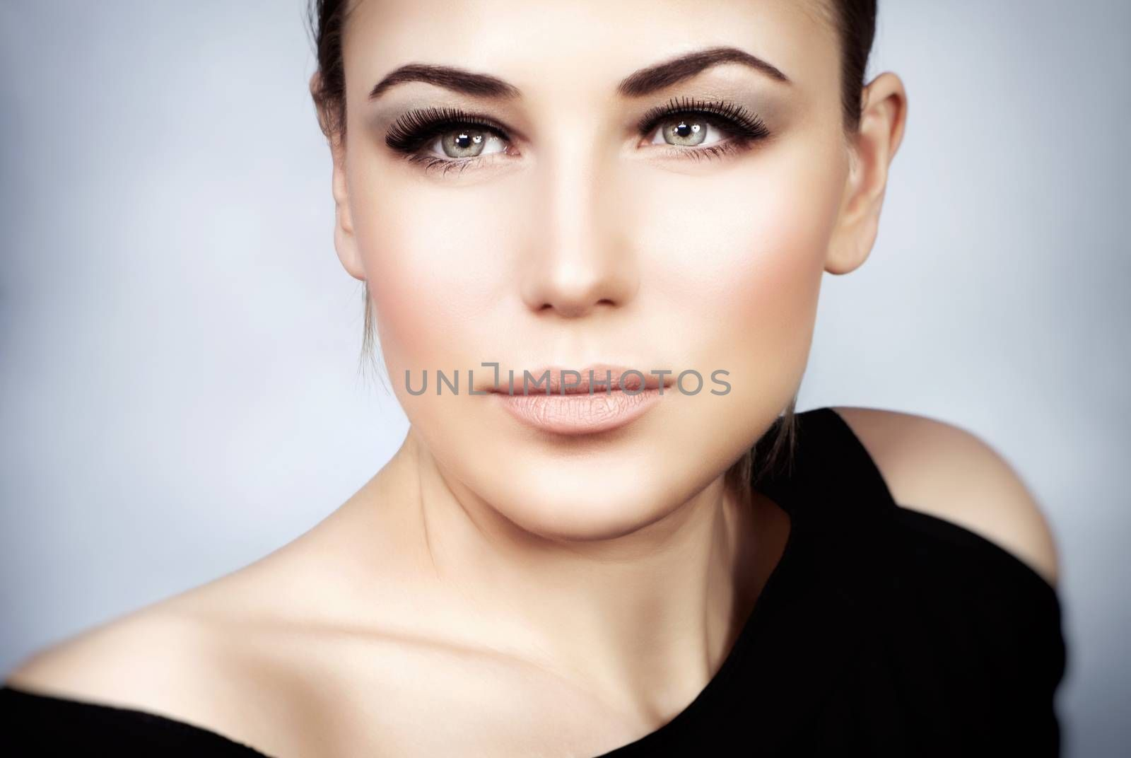 Closeup portrait of a beautiful woman with stylish makeup over gray background, smoky eyes and perfect skin tone, gorgeous seductive model