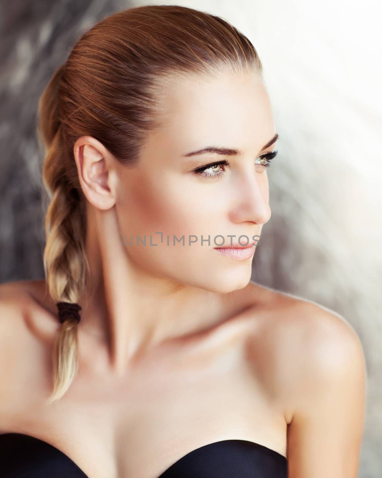 Portrait of a beautiful woman with natural makeup and stylish braid hairstyle looking aside, authentic beauty, fashion look of a gorgeous young model with perfect skin