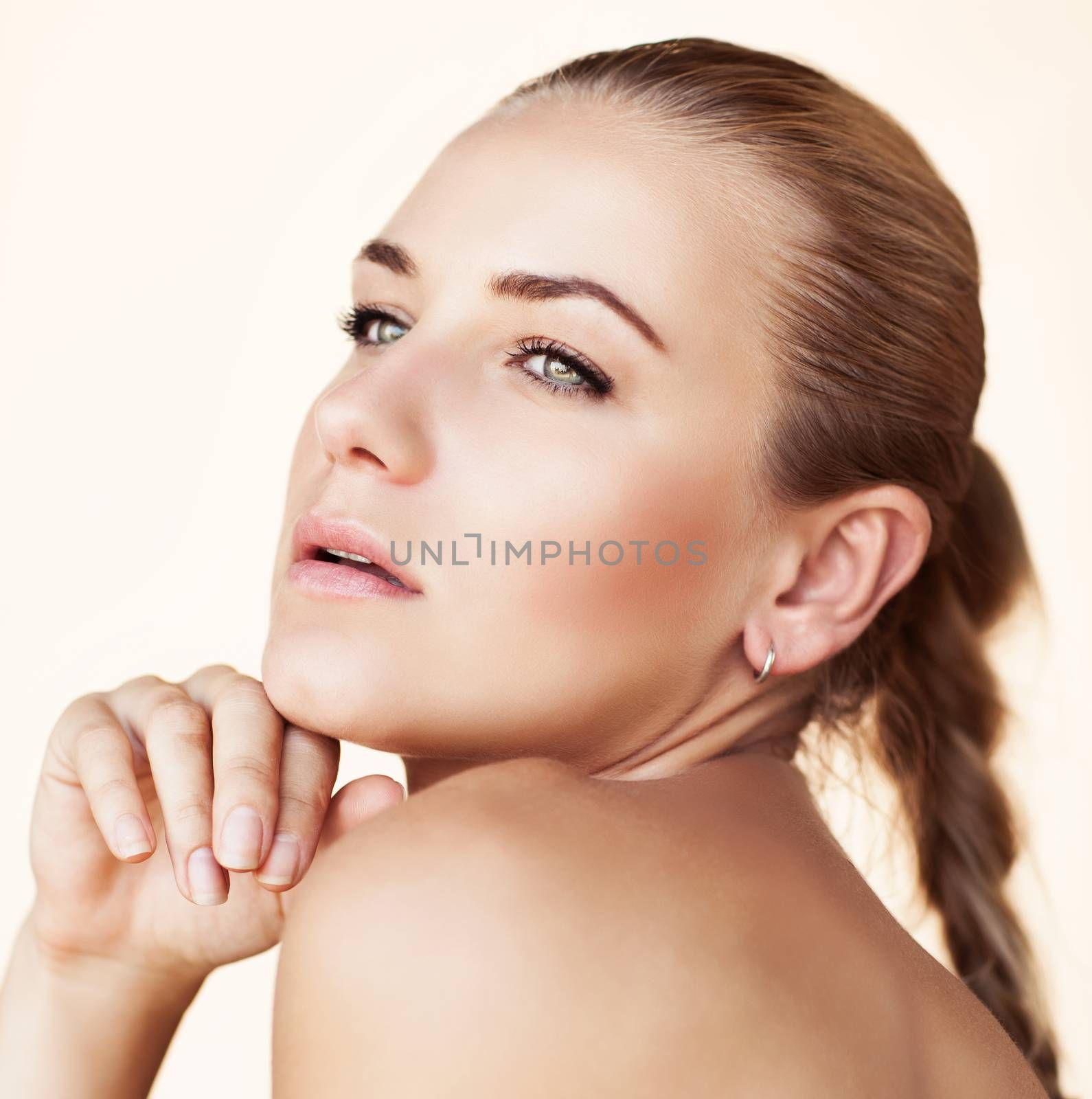 Closeup portrait of a gorgeous seductive female with natural makeup and scythe hairstyle isolated on a beige background, authentic beauty