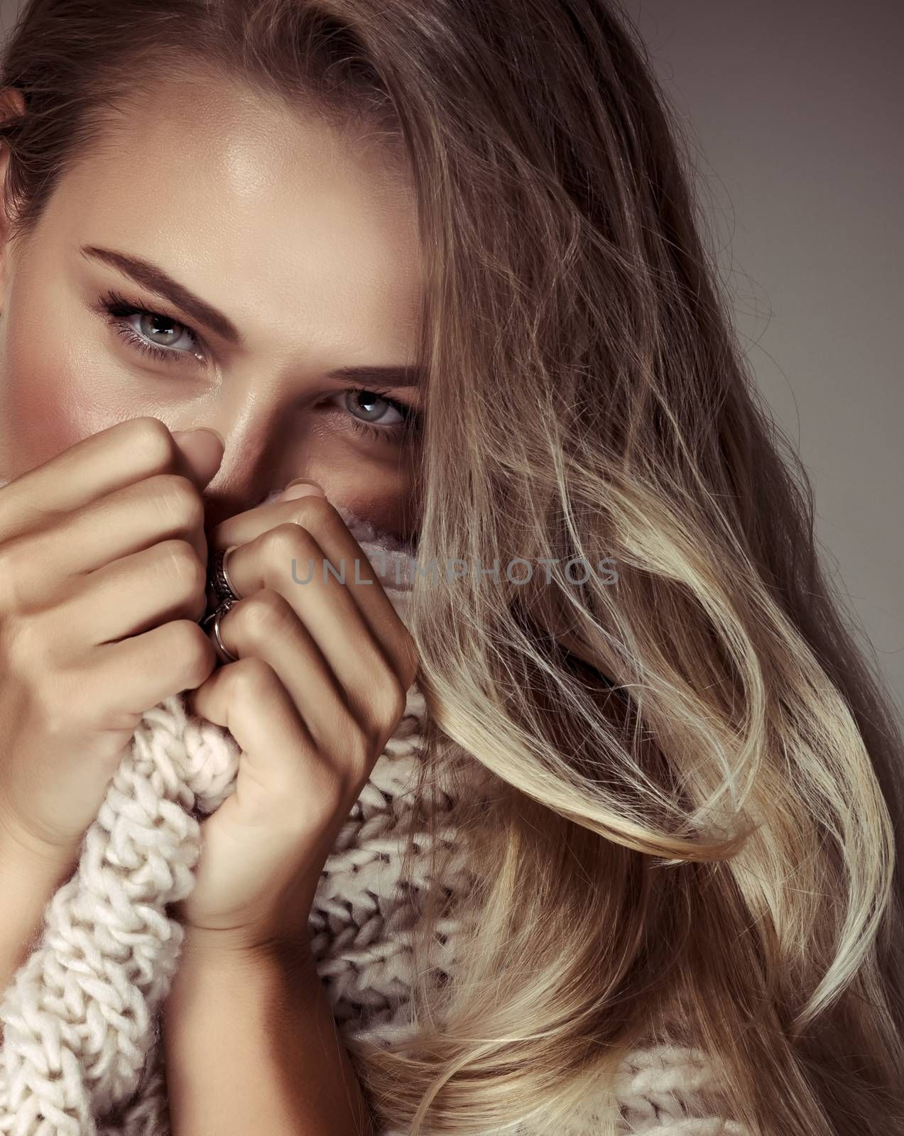 Fashion woman portrait, gorgeous sexy female closing mouth with big knitted scarf, stylish blond model, conceptual photo of a keeping secrets