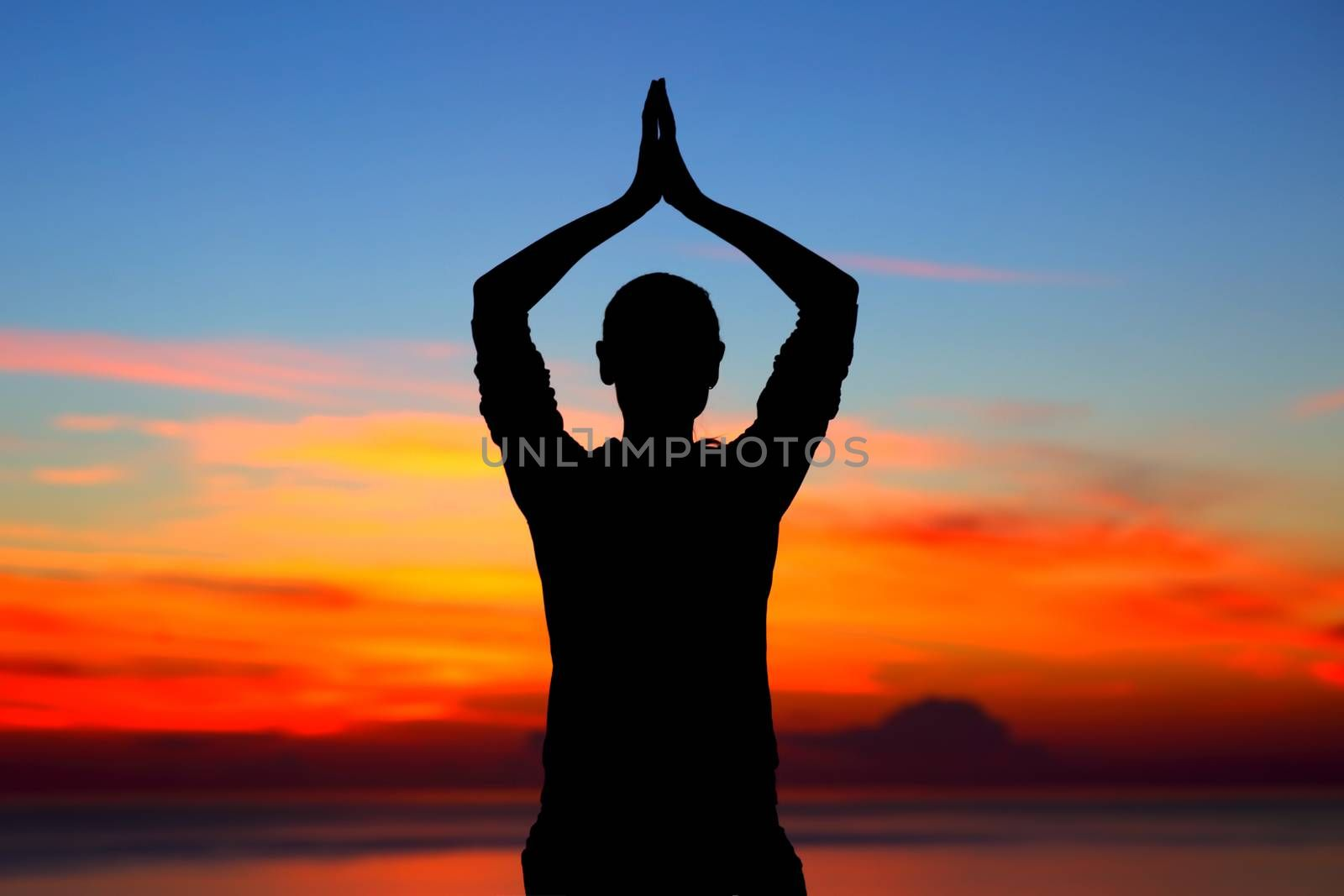Healthy woman doing yoga exercises outdoors, silhouette of a female meditating over beautiful sunset background, sport and mental health concept