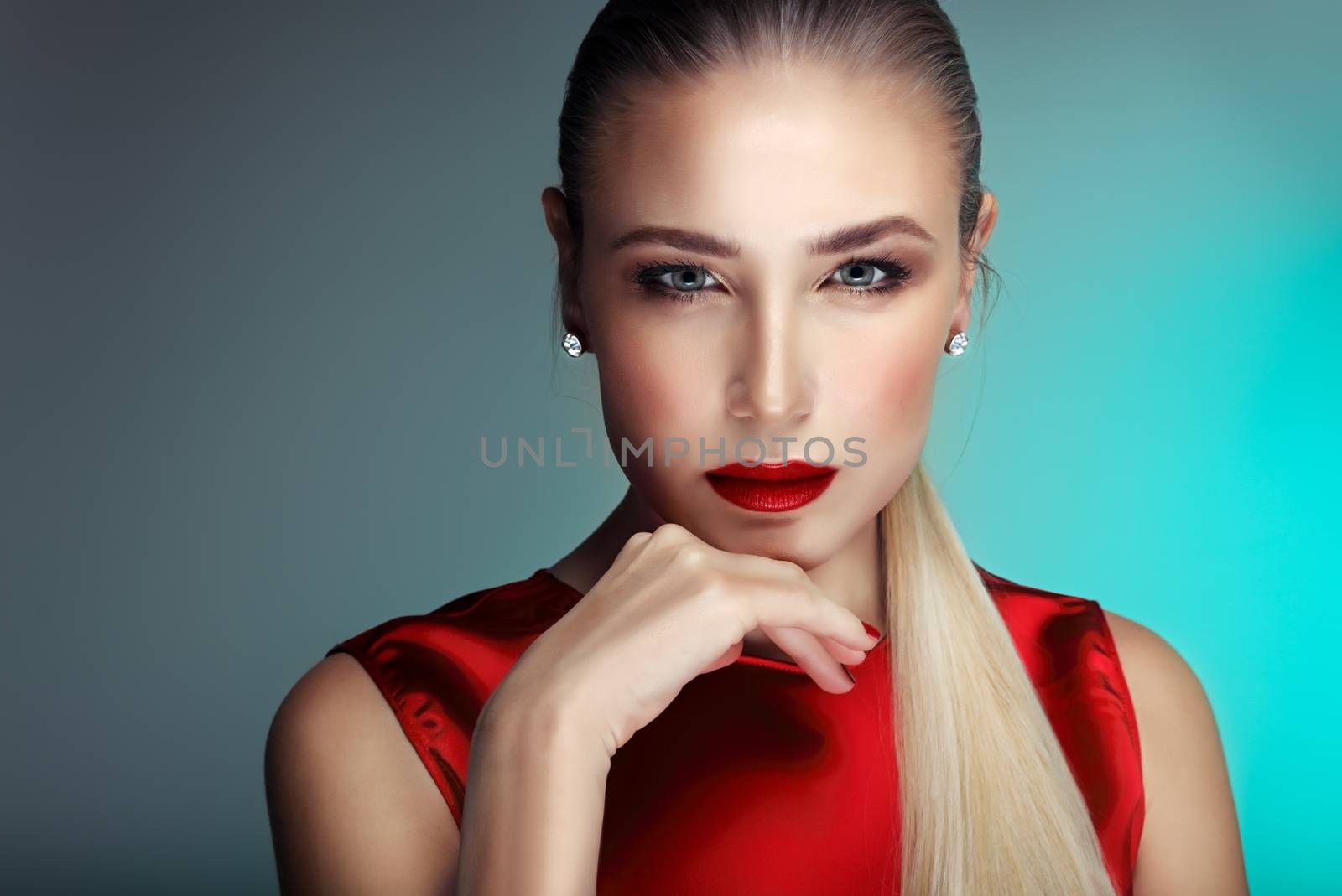Portrait of a beautiful gorgeous blond woman with perfect evening makeup isolated on blue background, sexy model with red seductive lips wearing red stylish blouse, luxury look for party
