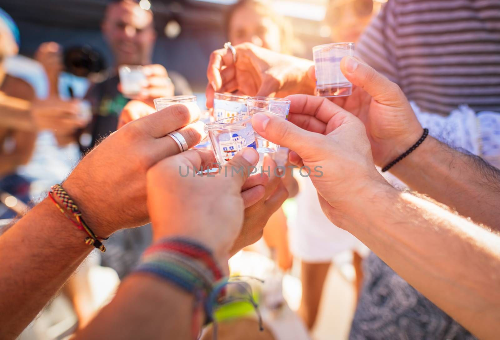 Closeup photo of a men hands with glass full of alcoholic drink, speaking toast, cheers, celebrating holiday, open air party, happy summer vacation