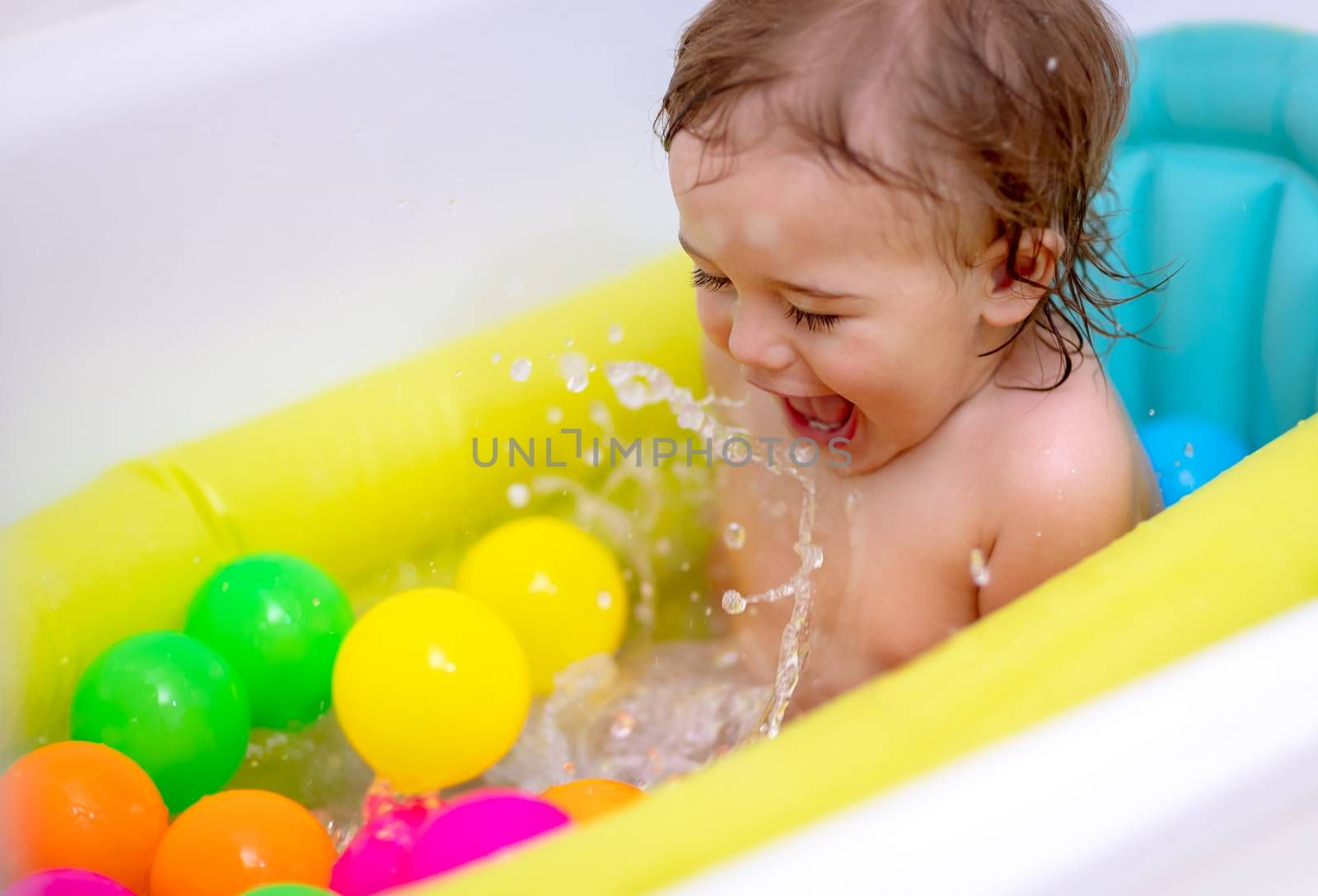 Cute happy little boy bathing in the child's tub, splashes water and enjoys it, healthy childhood, babies hygiene concept