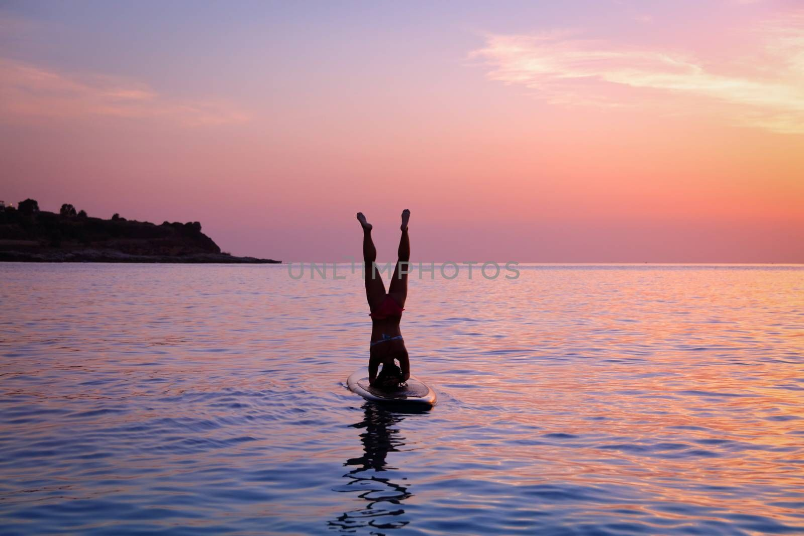 Silhouette of a sportive woman doing yoga exercise on the sup board over sunset, doing Sirsasana, headstand, active lifestyle, enjoying water sport, active summer vacation