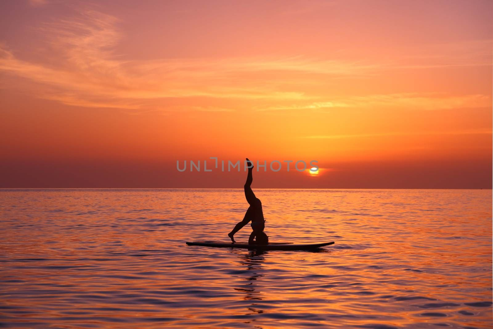 Silhouette of a yoga teacher balancing on paddle board over beautiful orange sunset background, standing on the head, doing Sirshasana on the beach