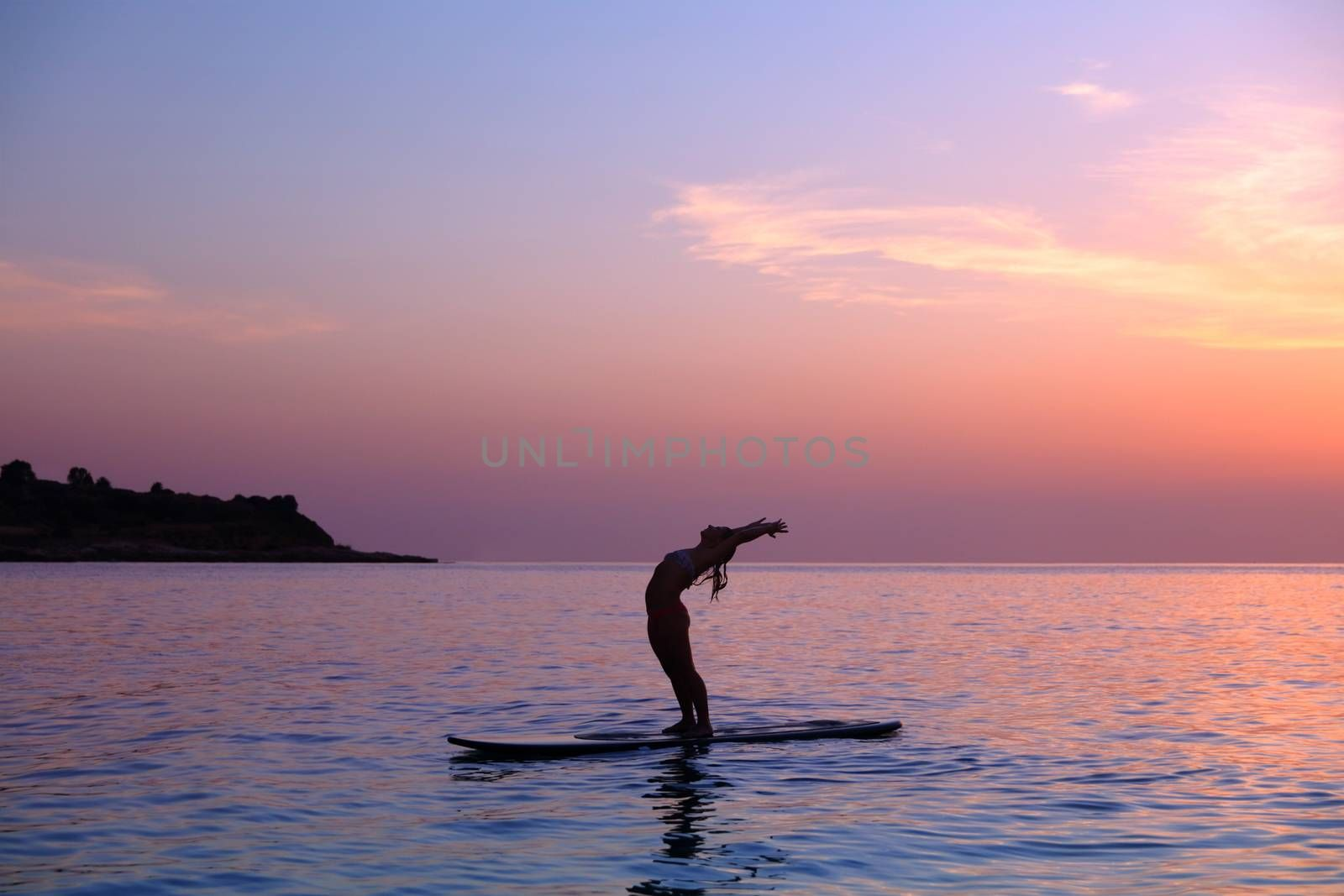 Silhouette of a sportive woman doing yoga exercise in the sea, balancing on the sup board over sunset, active lifestyle, enjoying water sport, active summer vacation
