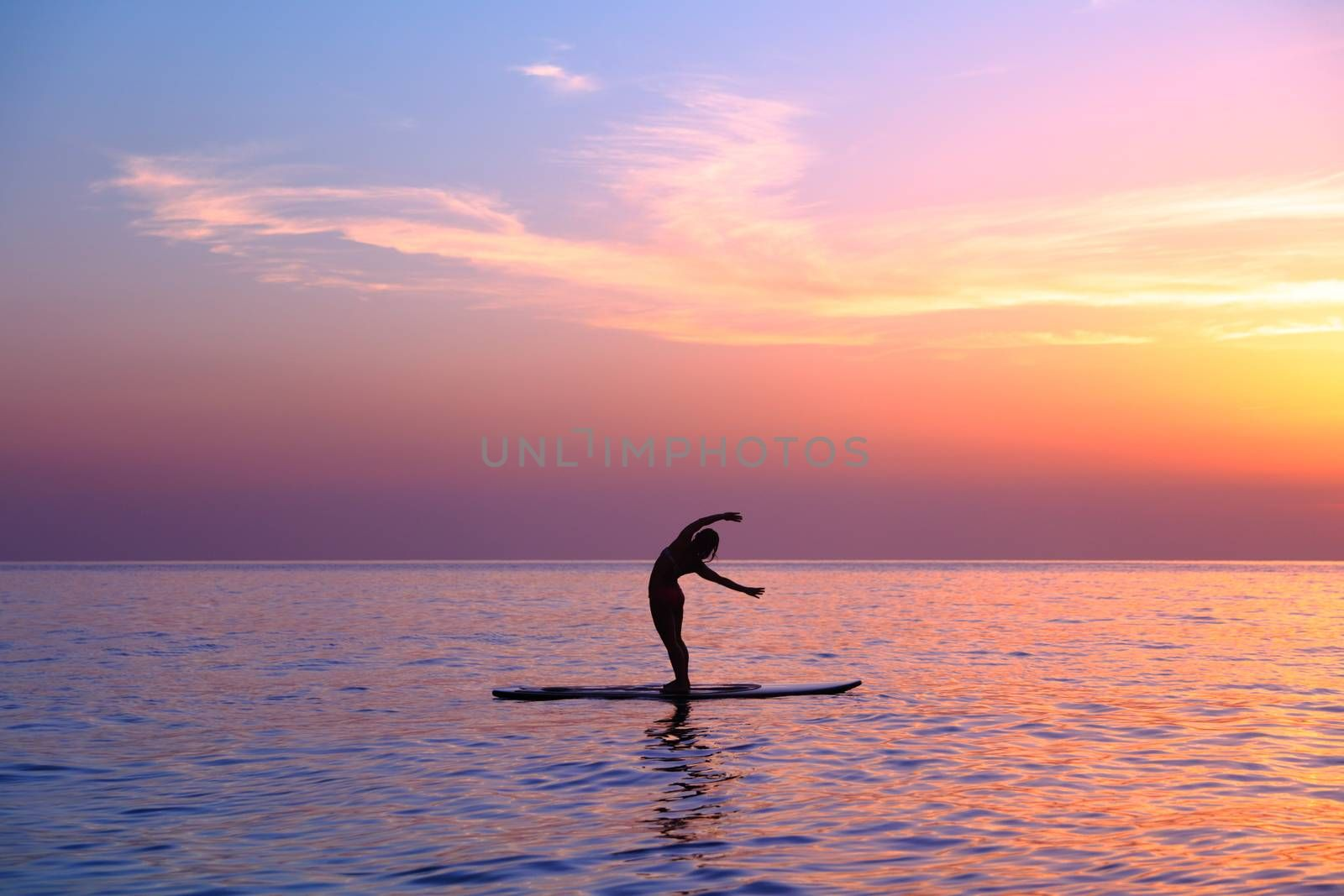 Silhouette of a yoga trainer over sunset background doing asanas, balancing on the sup board, enjoying healthy lifestyle, summer vacation on the beach