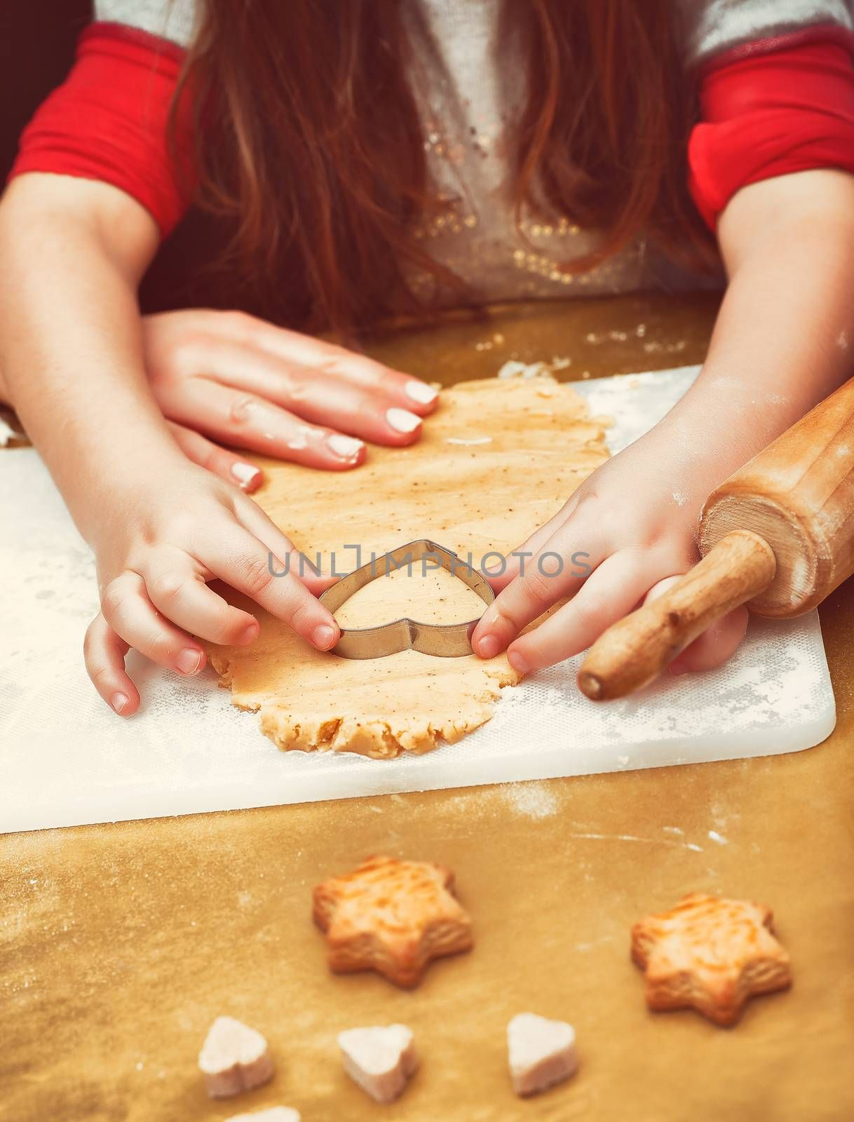 Little girl with mother's help making tasty sweet homemade cookies, gingerbread, traditional Christmas sweets, good Christmastime family tradition