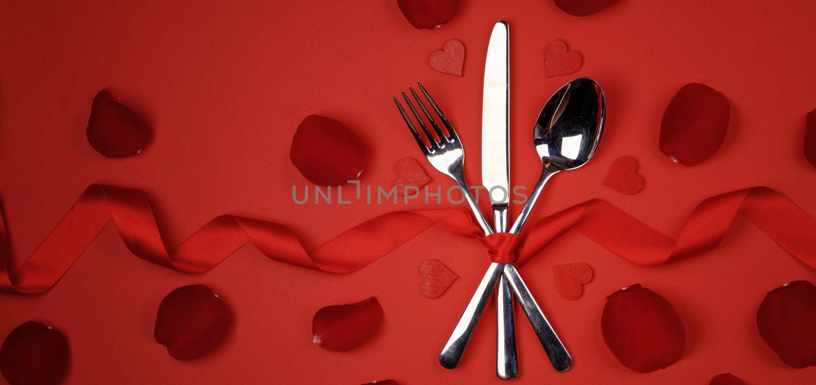 Cutlery set tied with silk ribbon rose petals and hearts on red background Valentine day romantic dinner concept