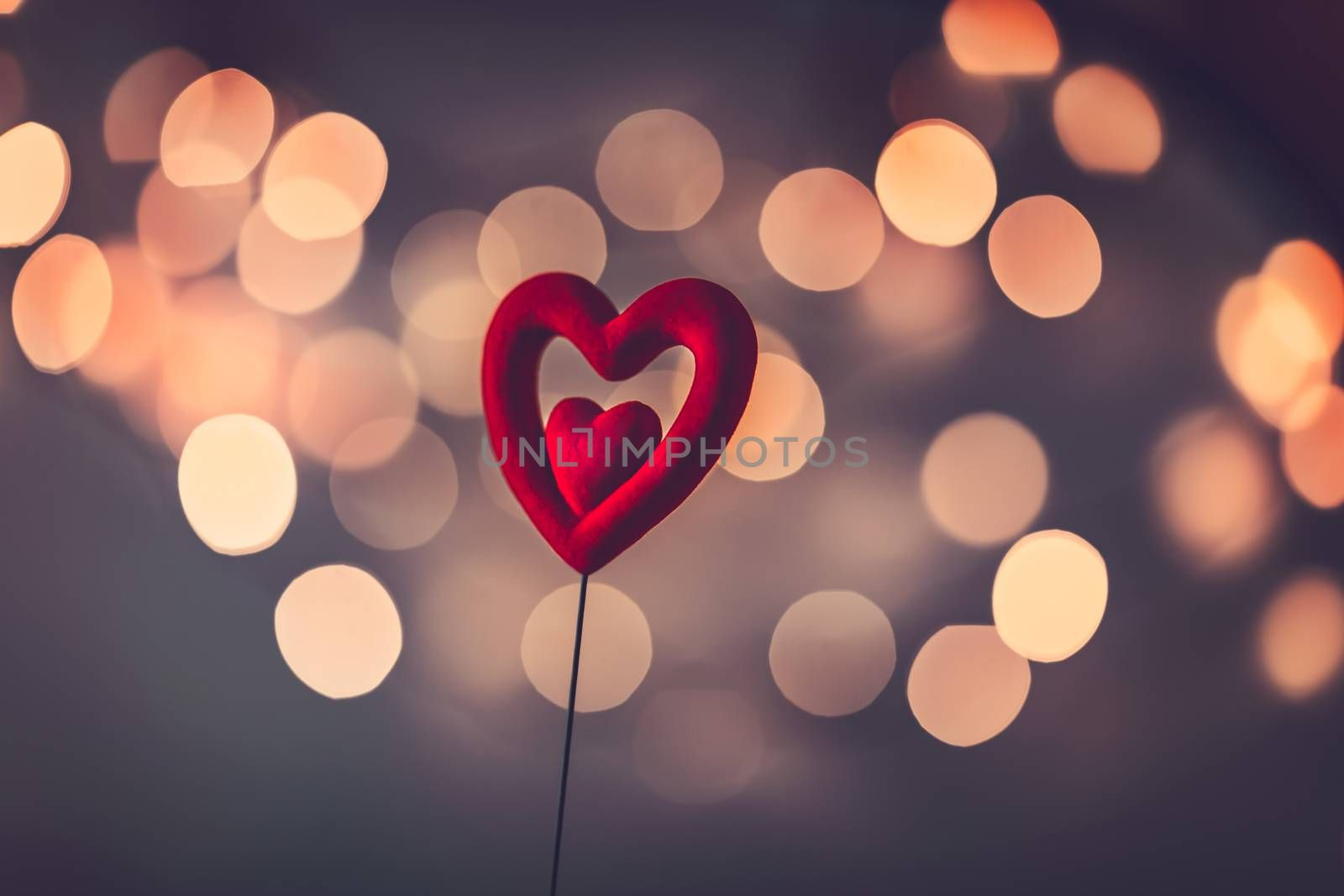 Beautiful red heart over blurry vintage bokeh background, romantic greeting card for Valentine's day, love concept