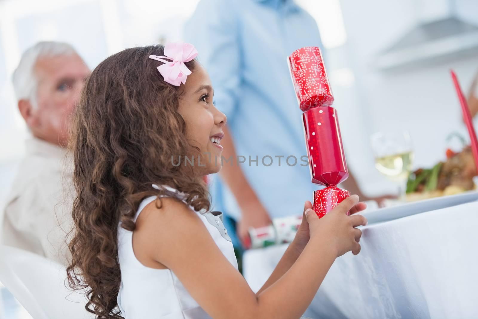 Cute little girl holding crackers at table for christmas dinner