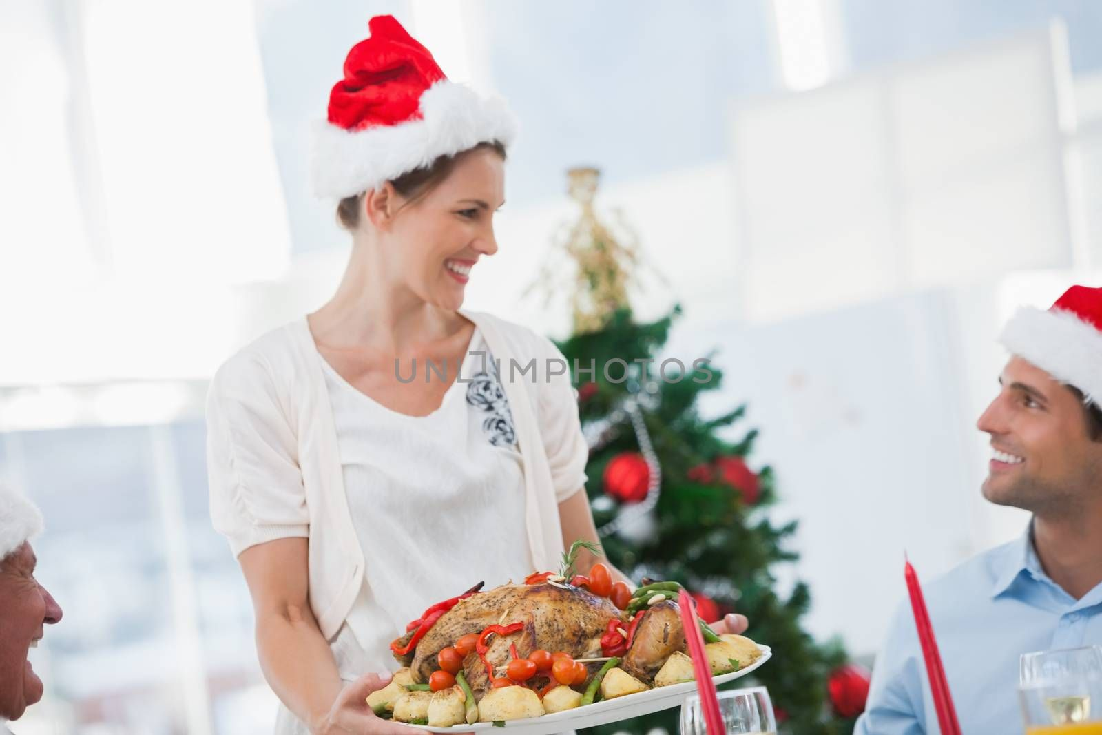 Cheerful woman wearing santa hat and bringing a roast chicken at a christmas dinner