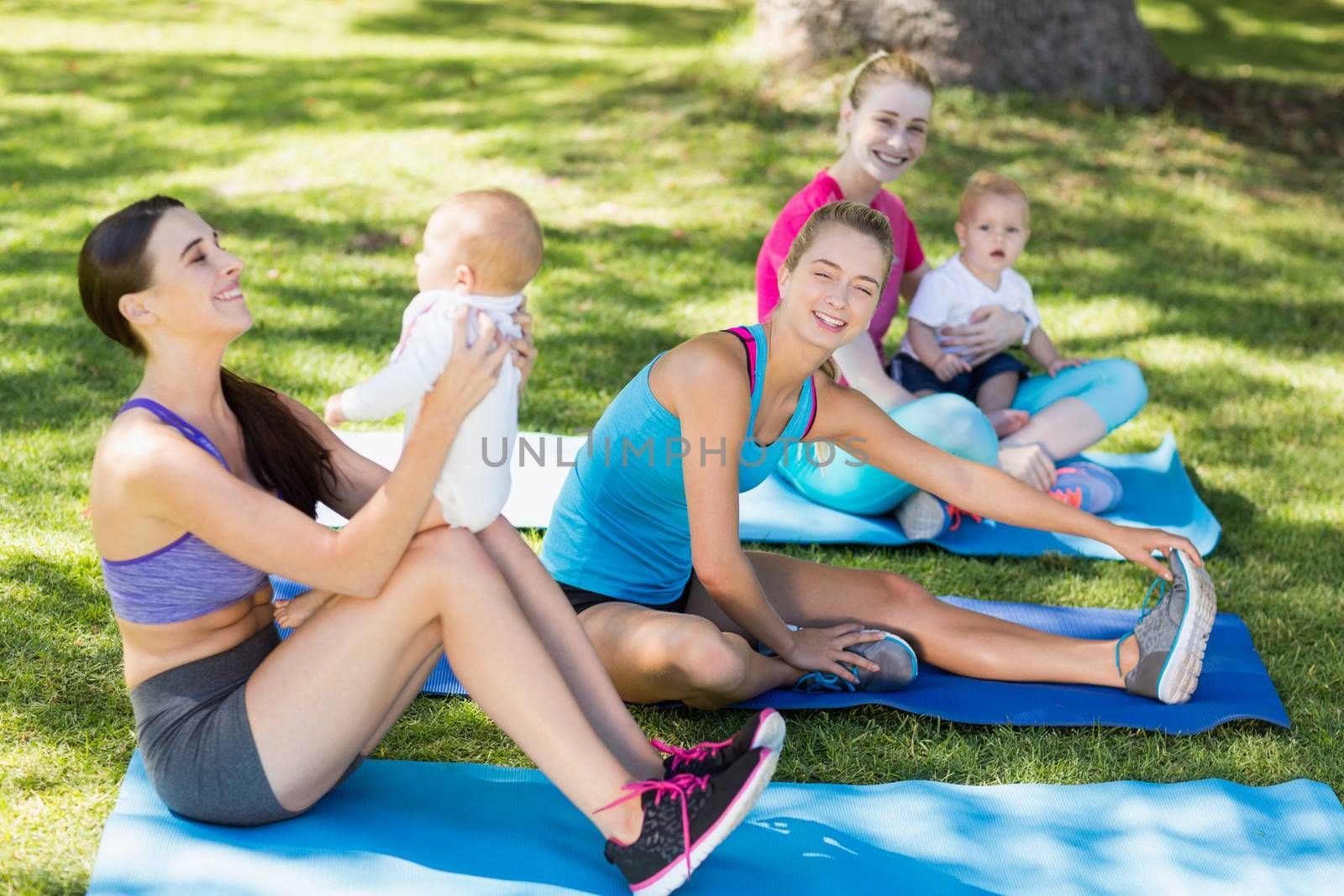 Women holding their babies while exercising in park