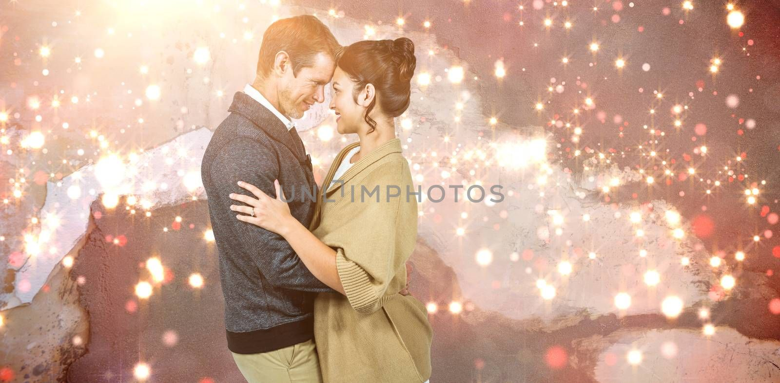 Side view of romantic couple hugging against blurred red light