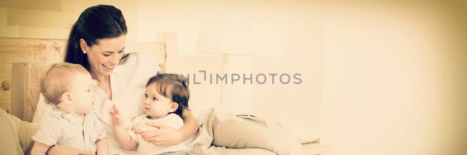 Happy mother with cute babies on bed at home