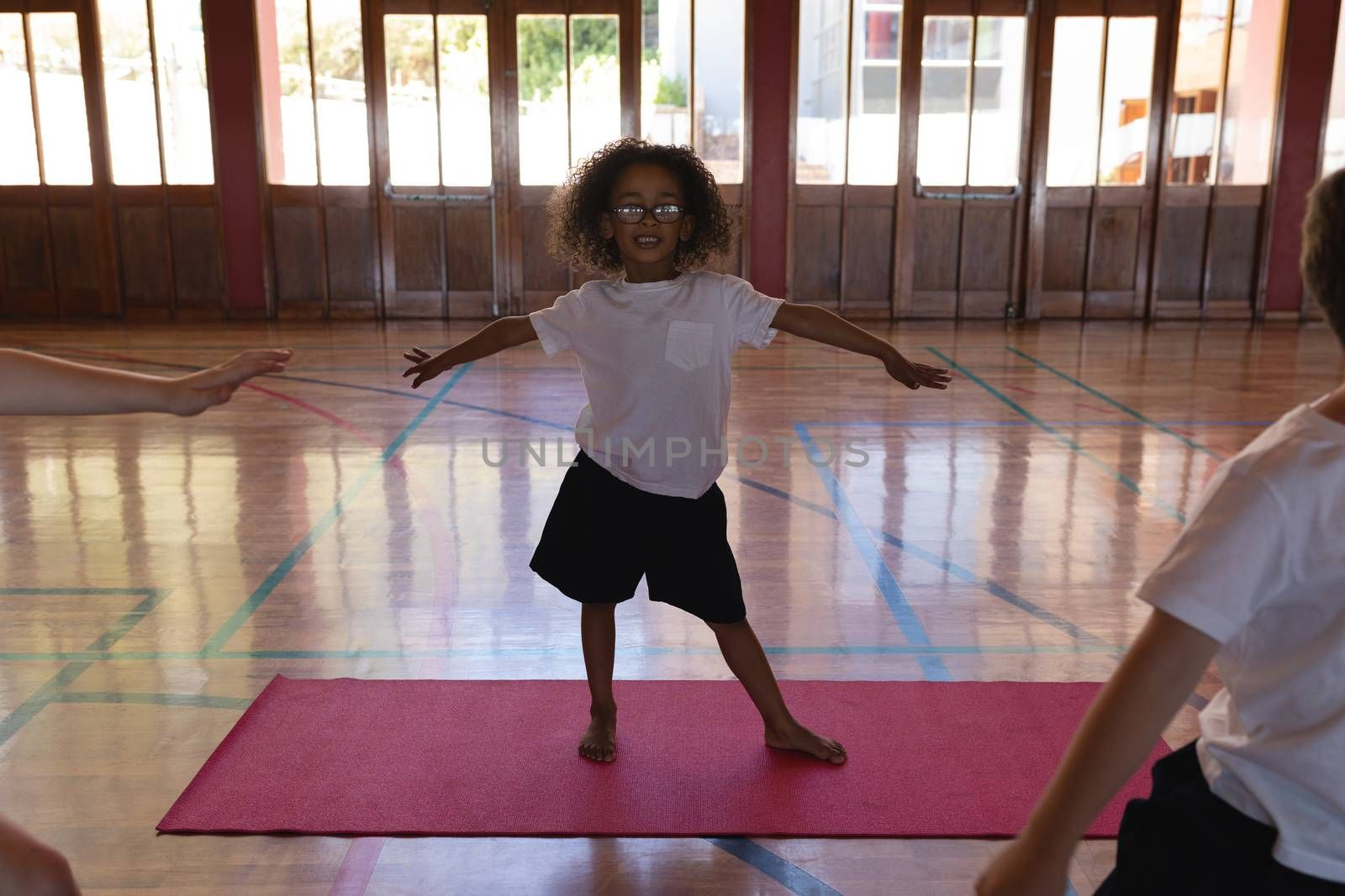 Front view of schoolgirl doing yoga with smile on a yoga mat in school