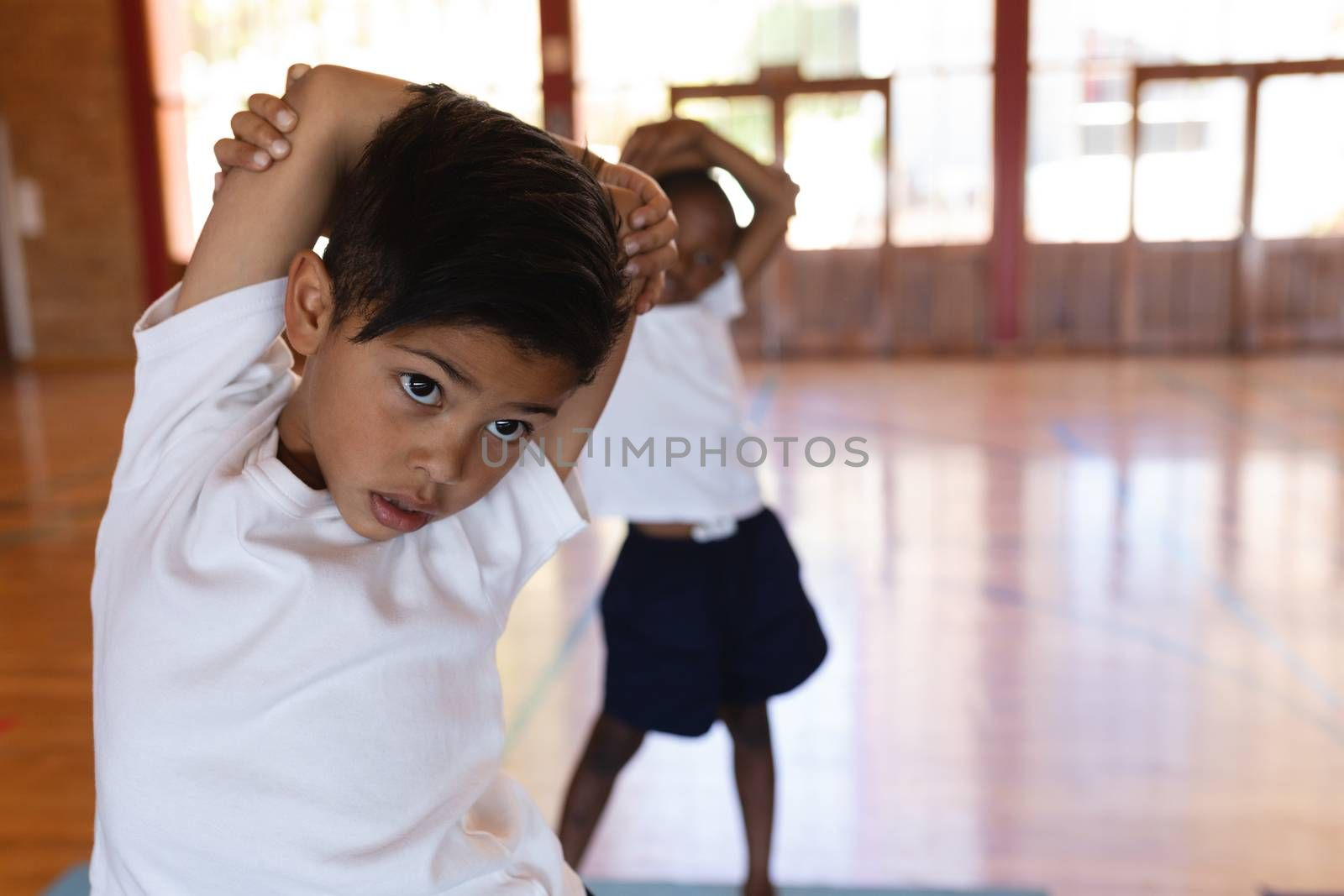 Front view of schoolboy doing yoga on a yoga mat in school