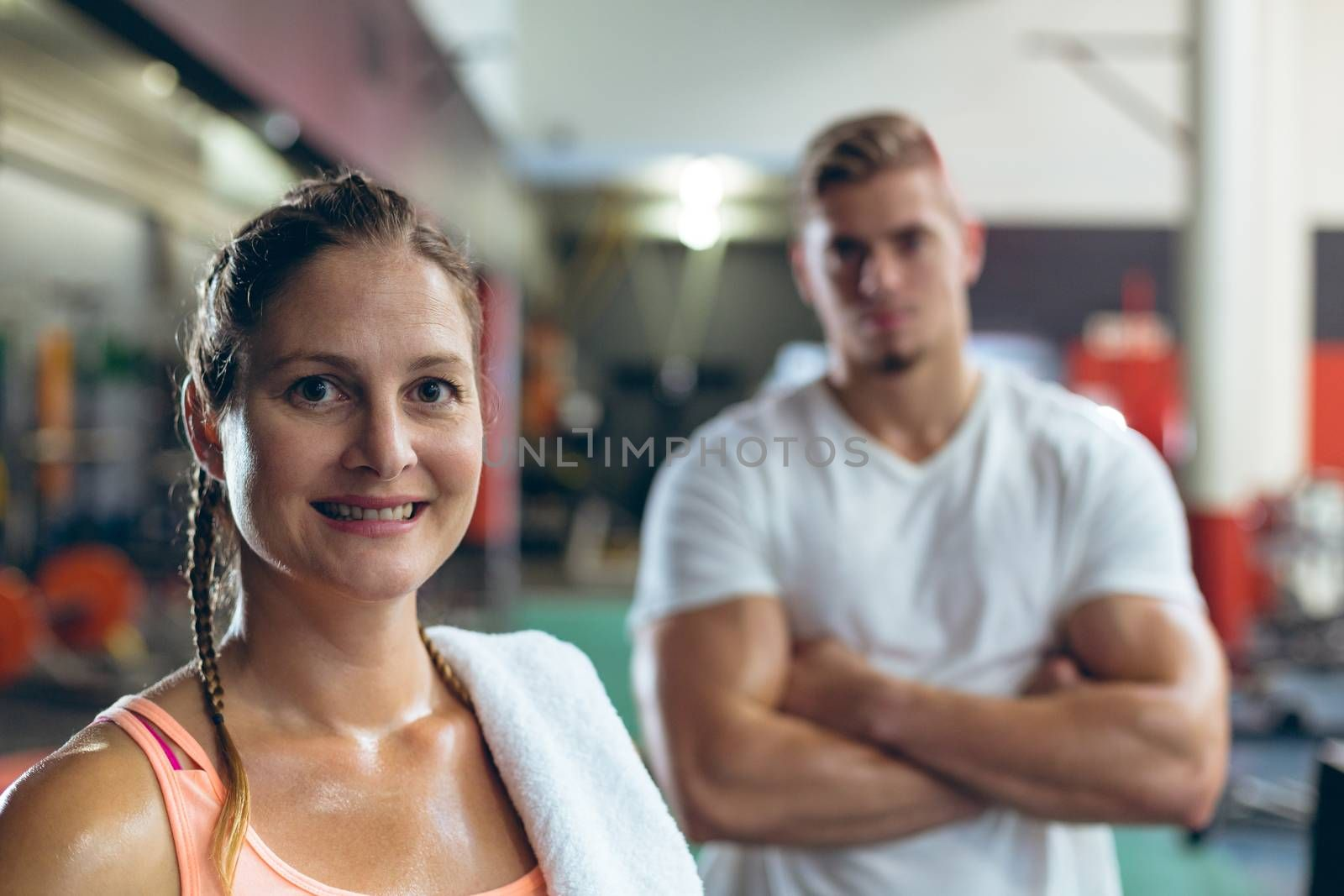 Portrait close-up of pretty Caucasian female athlete looking at camera in fitness center. Handsome young Caucasian man is standing in the background. Bright modern gym with fit healthy people working out and training