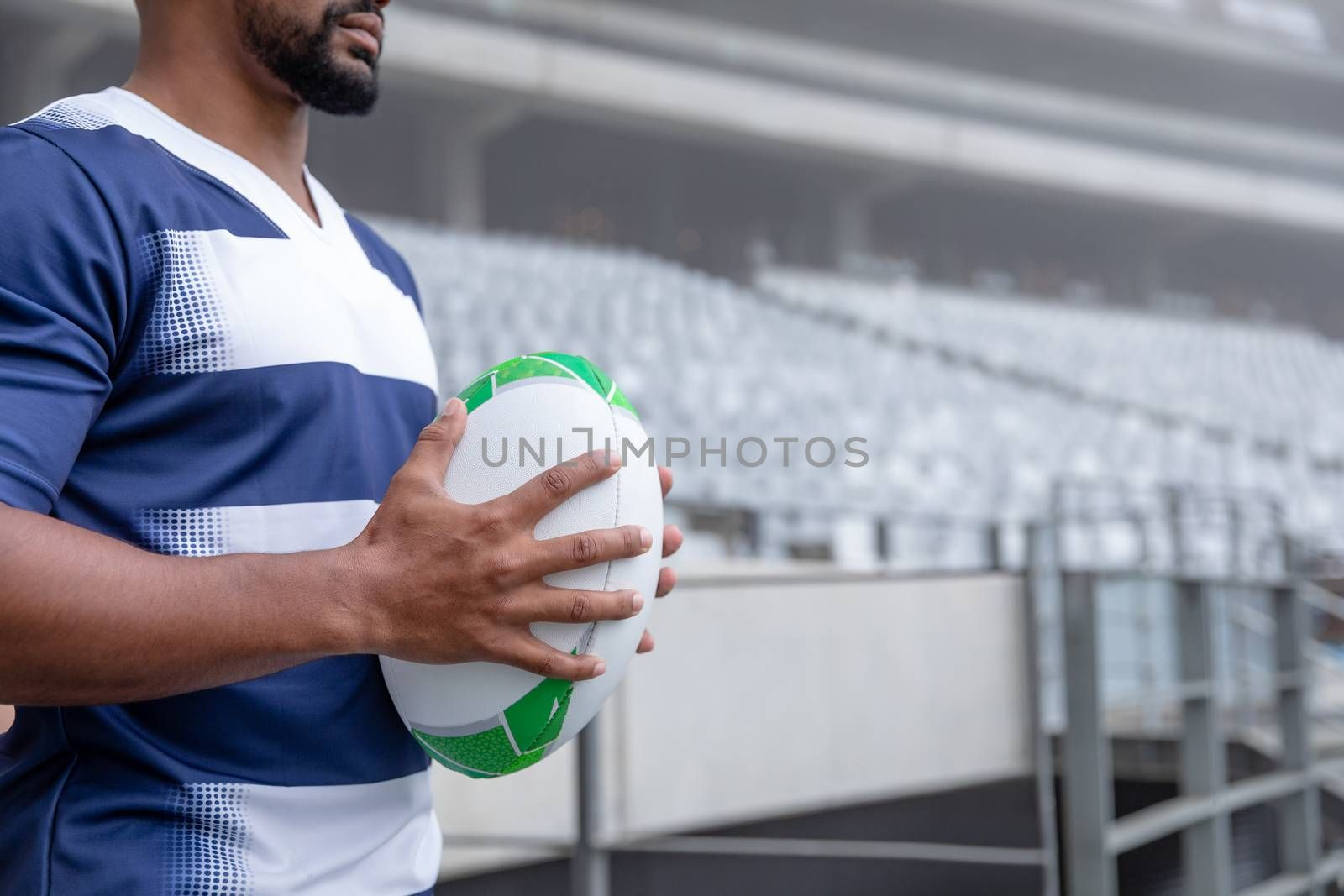 Mid section of African American male rugby ball player holding a rugby ball in stadium